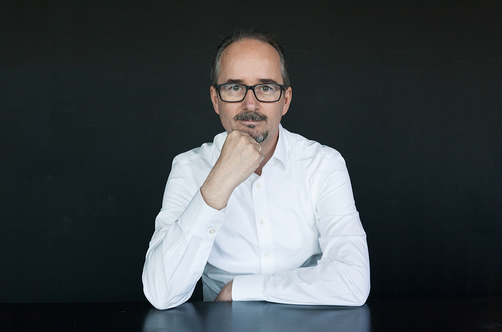 Christoph Rohrer wears a white shirt and leans on the table.
