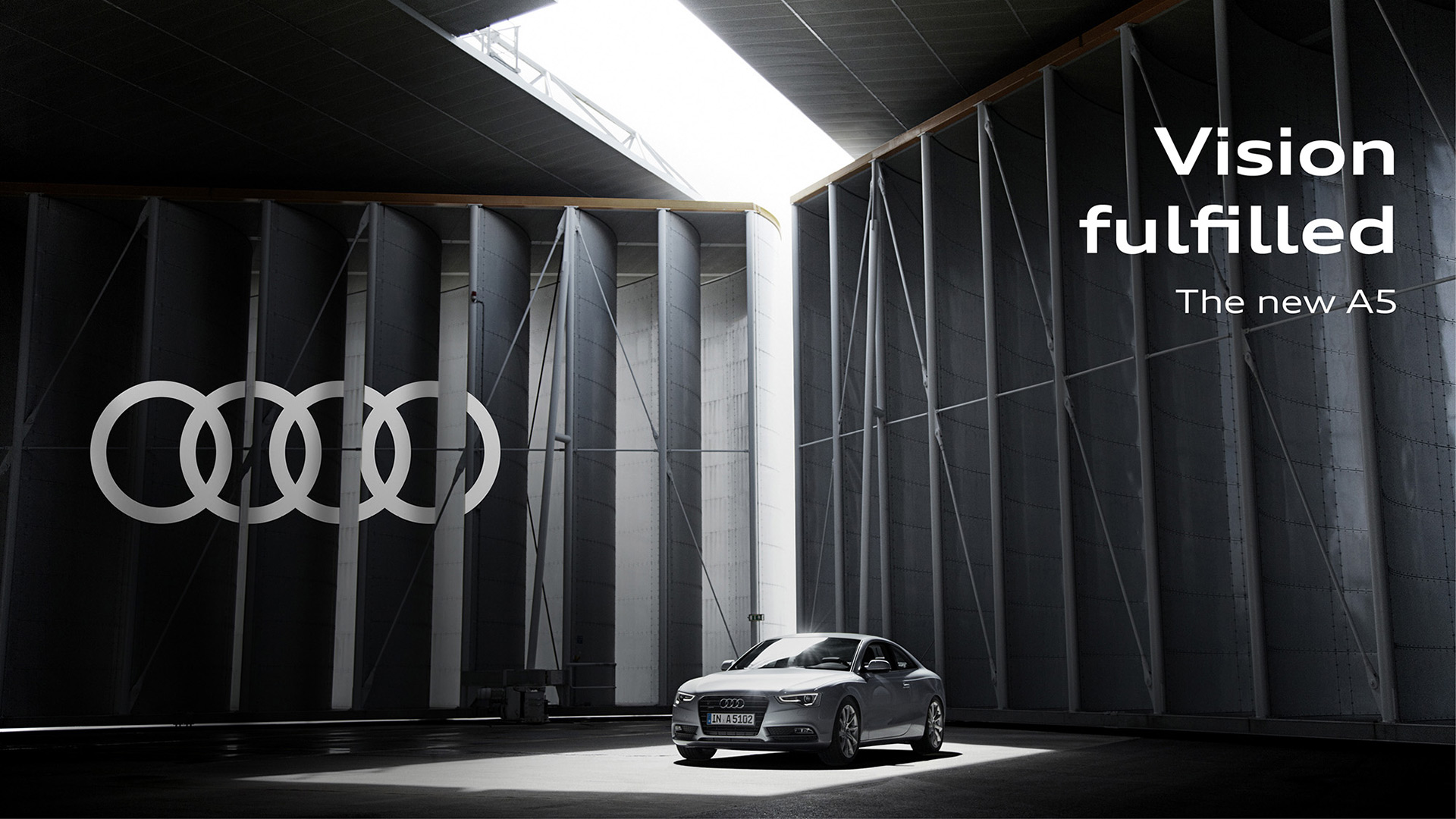 Advertising for the new A5 from Audi. The car stands in front of a revolving wall on which the Audi logo can be seen on the left. Daneben steht: Vision fulfilled. The new Audi A5.