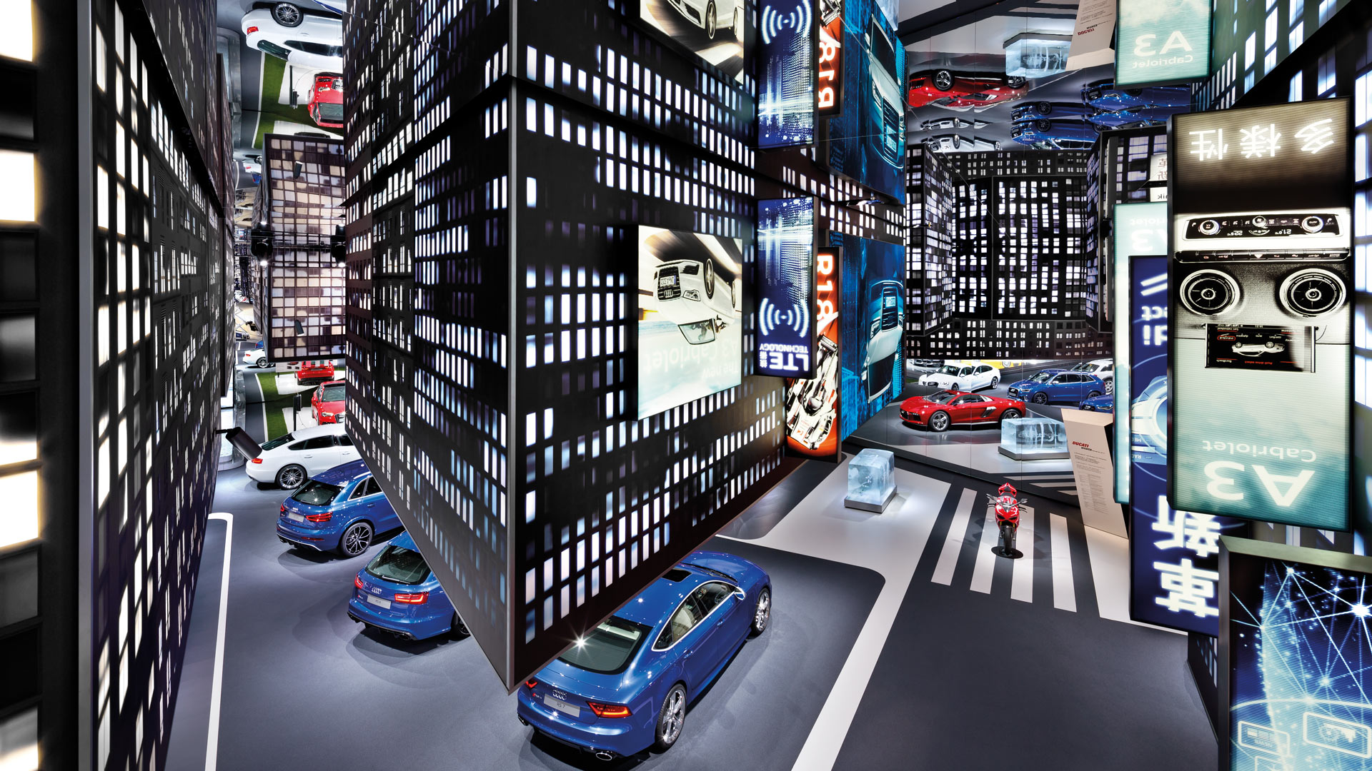 A view from above shows the hanging office buildings and the Audi models standing on the floor.