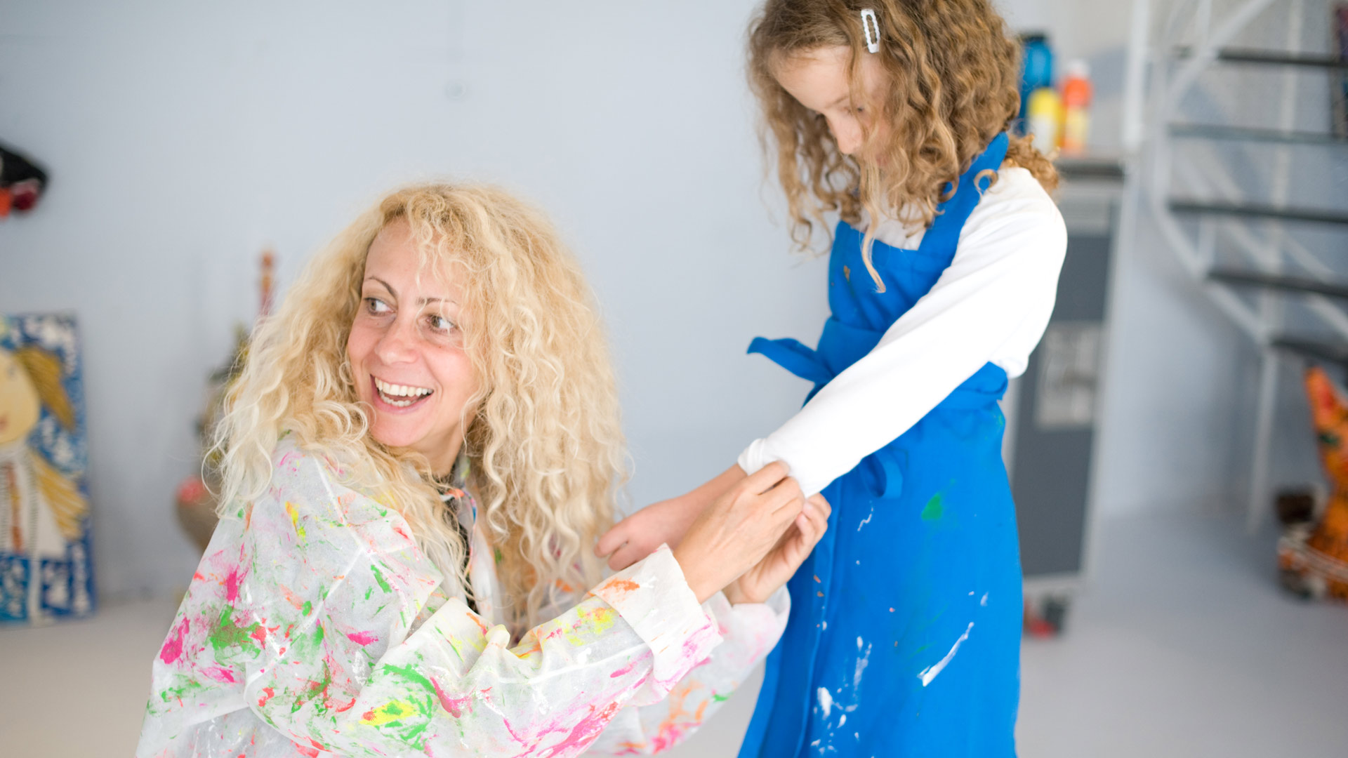Elena Janker helps a little girl roll up her sleeve.