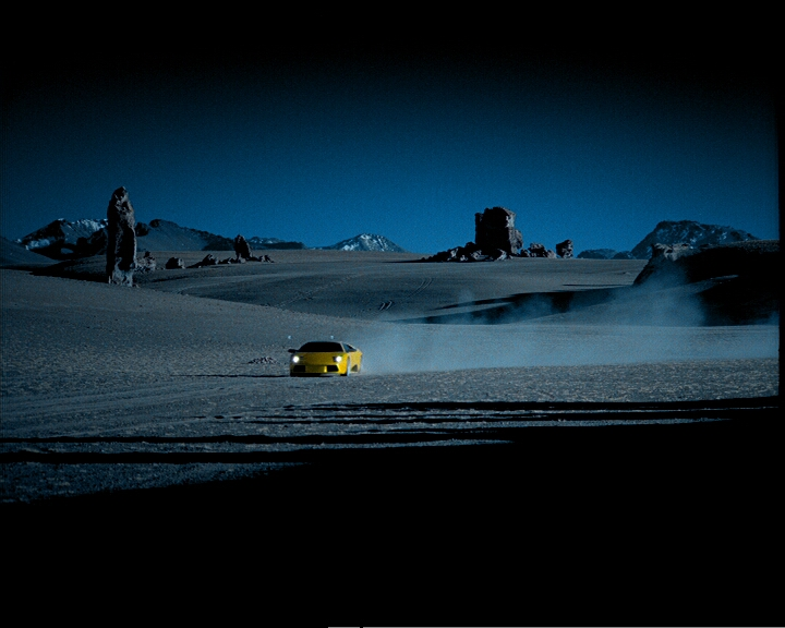A yellow Lamborghini drives lonely through the landscape on the ätna and pulls a cloud of dust behind him.