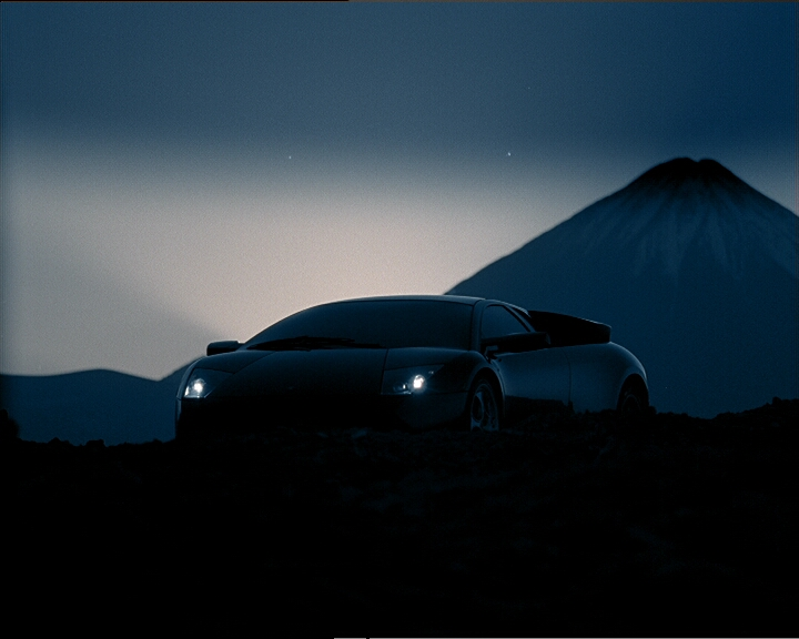 The Lamborghini stands before the Etna at dusk.