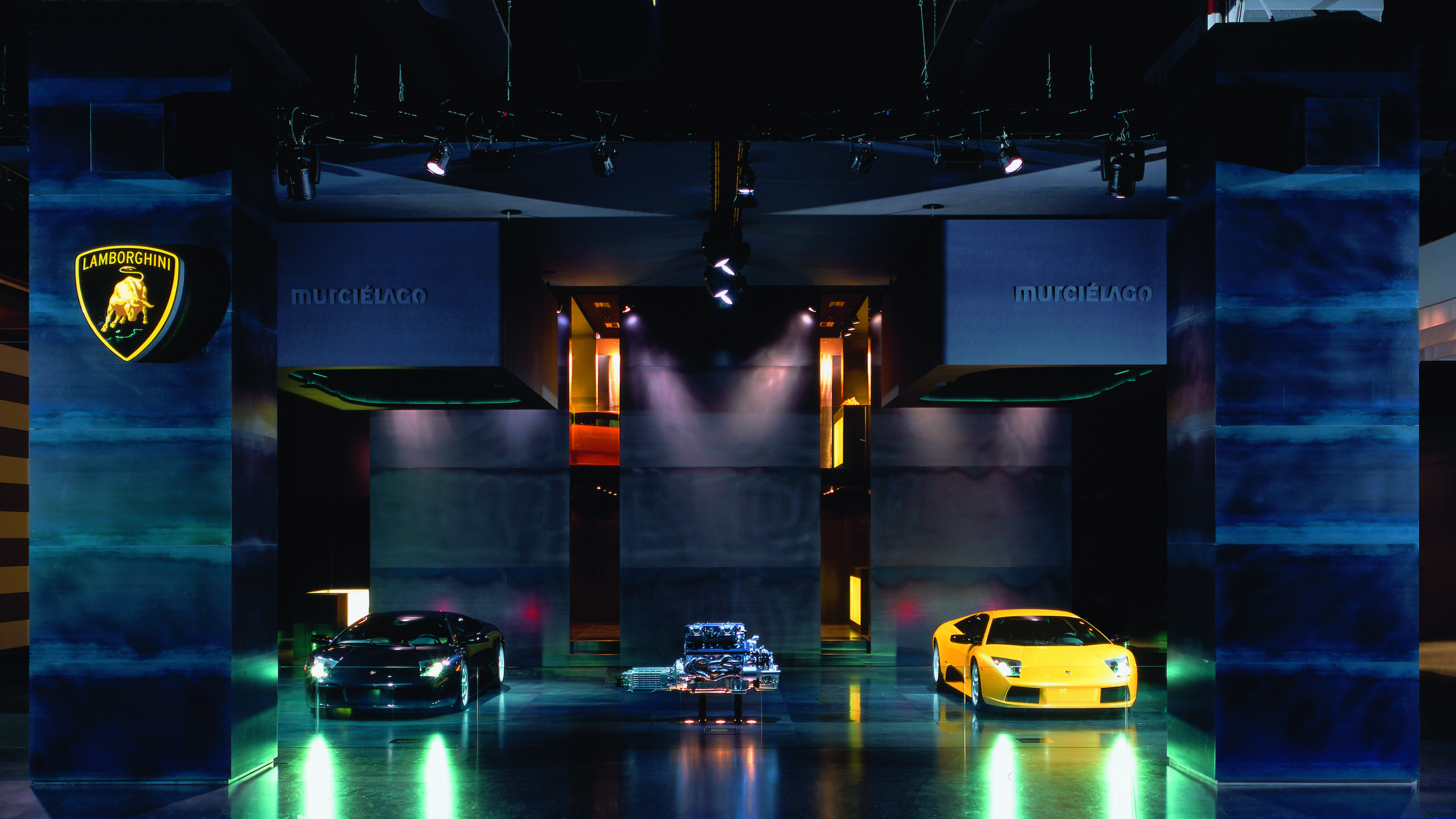 A Lamborghini engine is staged at an exhibition stand between a black and a yellow Murcielago.