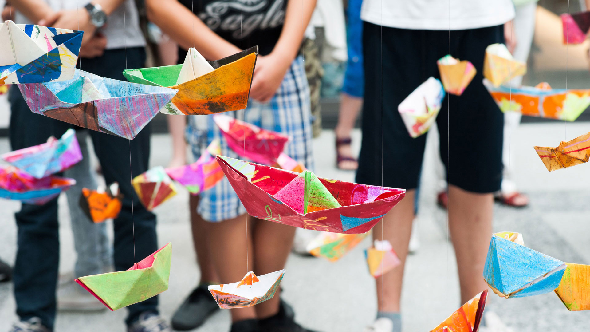 Children look at their colourful paper boats hanging on threads.