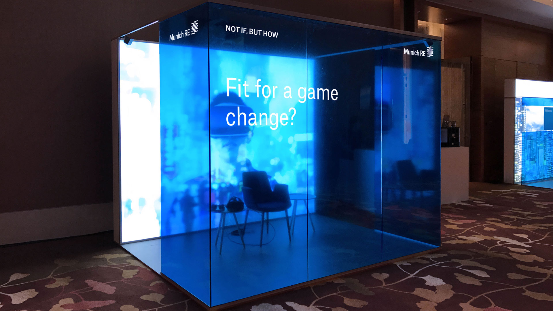 In a blue cube there is a chair and a table with VR glasses on it. On the blue glass pane is written: Fit for a game change?