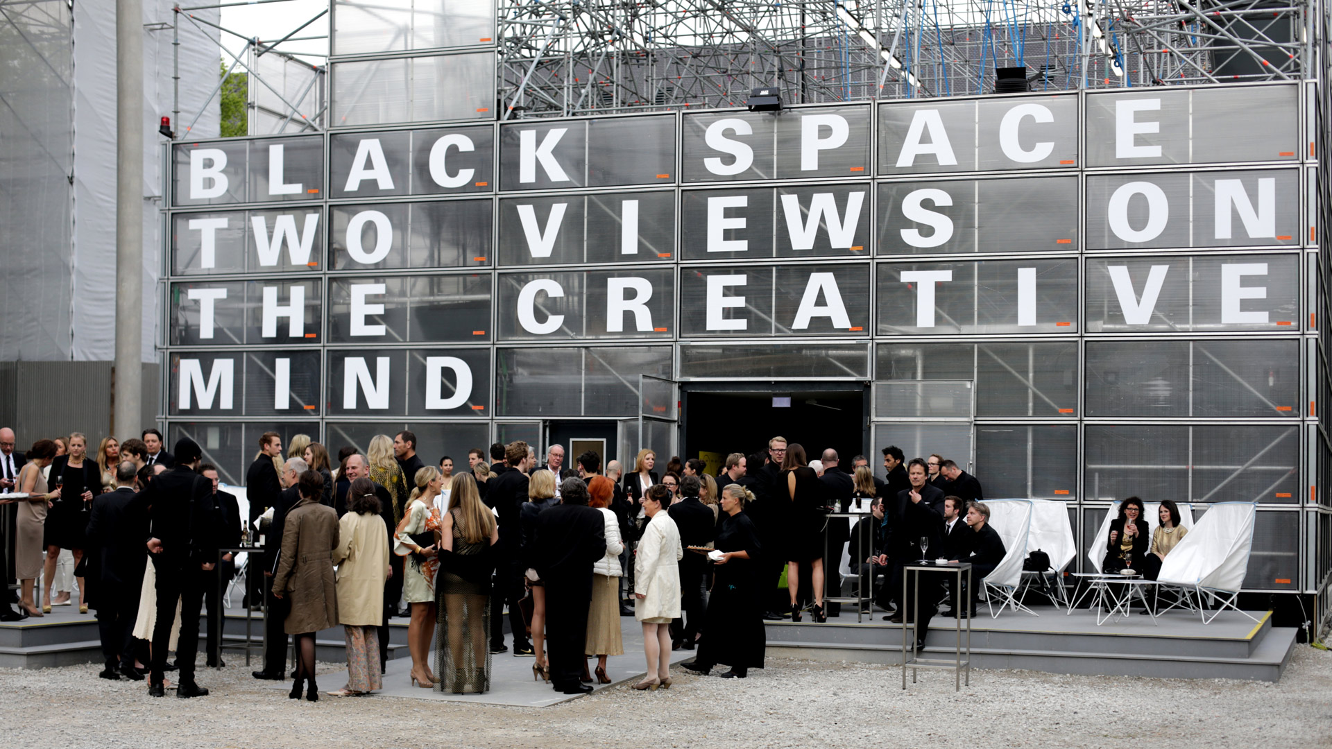 The invited guests, all dressed in black and gold, stand in front of the entrance to the Schaustelle.