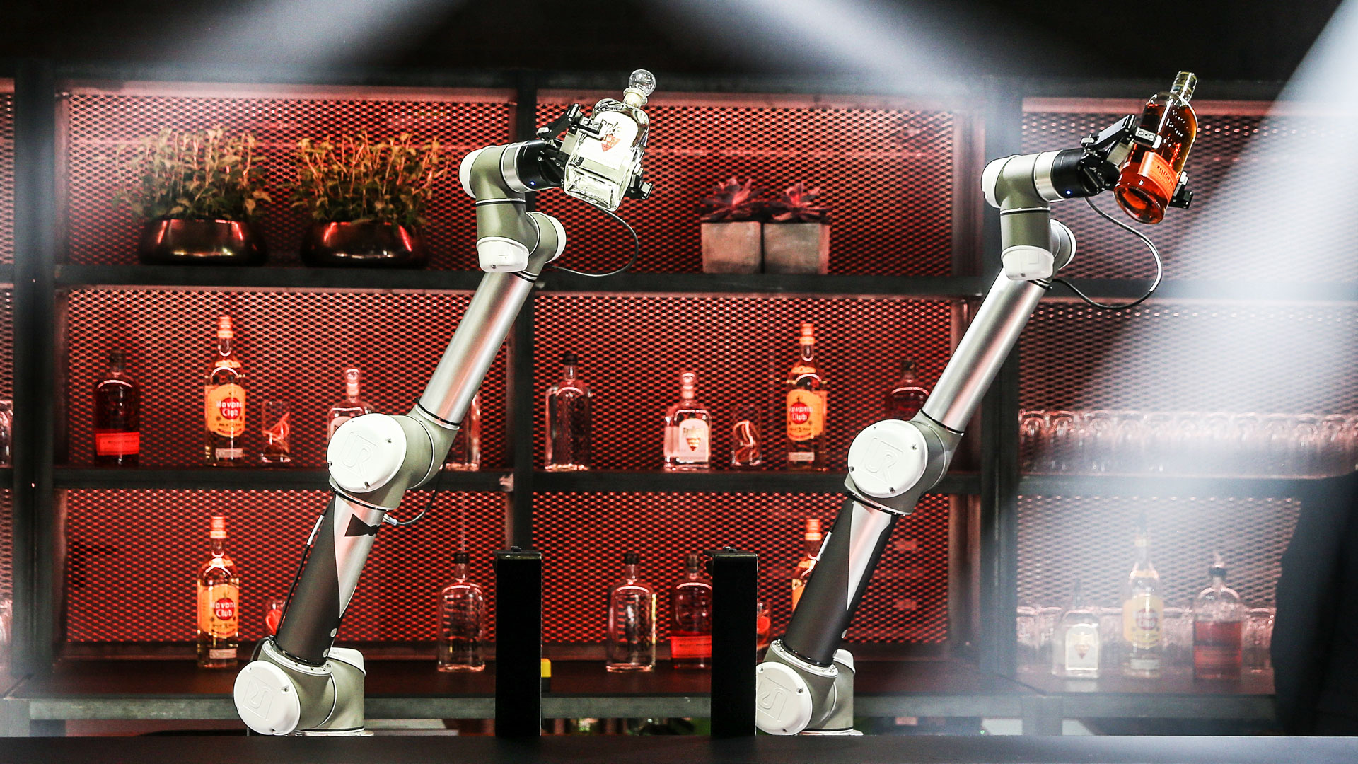 Two industrial robots take over the barkeeper function and mix the cocktails.