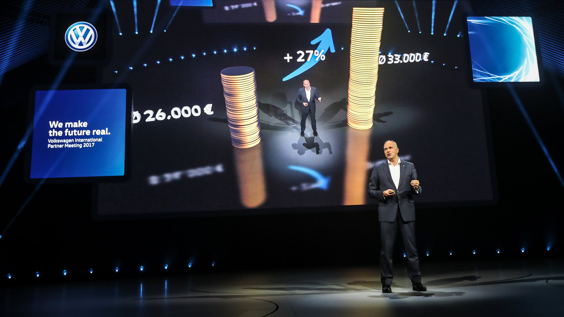 Volkswagen Sales Director Jürgen Stackmann stands on stage. Behind him you can see a screen on which two towers of coins are depicted by Augmented Reality.