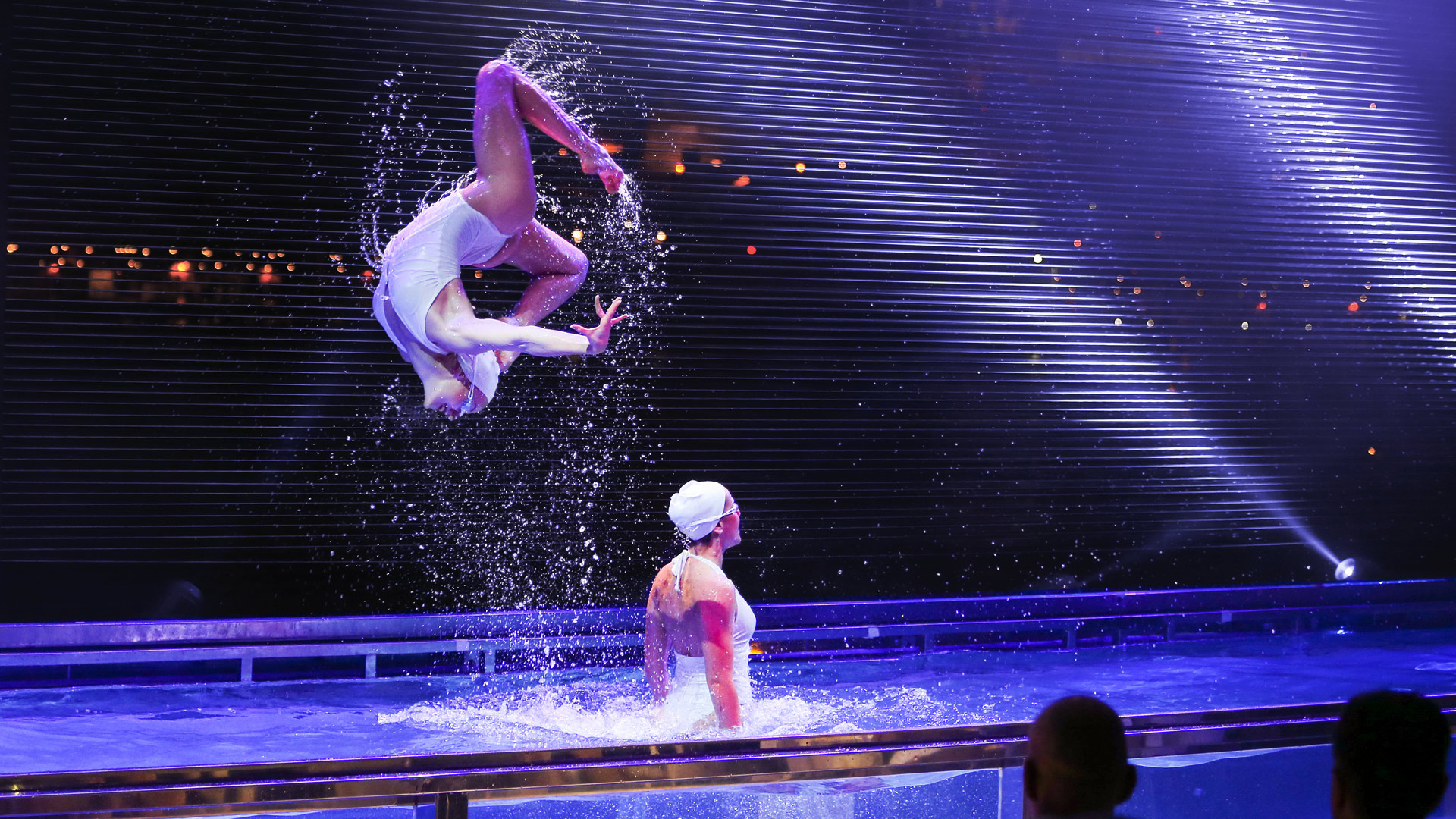 Two dancers in white swimsuits show a spectacular show in the stage pool.
