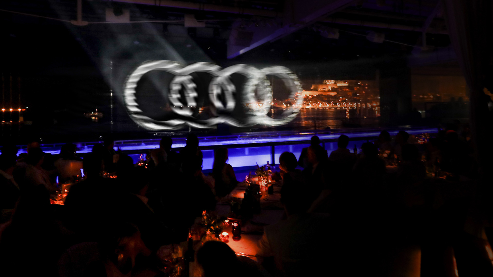 The guests of the award look through the transparent Audi logo made of nylon threads onto the illuminated old town of Ibiza.