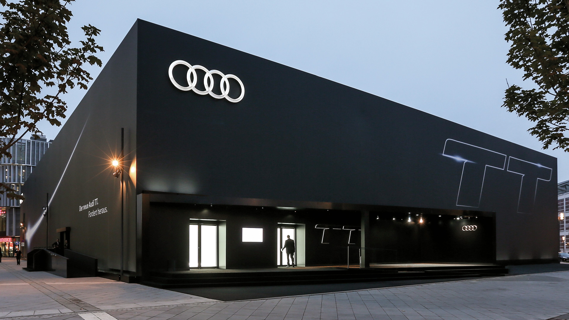 The black building from the outside. On the top left is the Audi logo, on the right two large Ts.