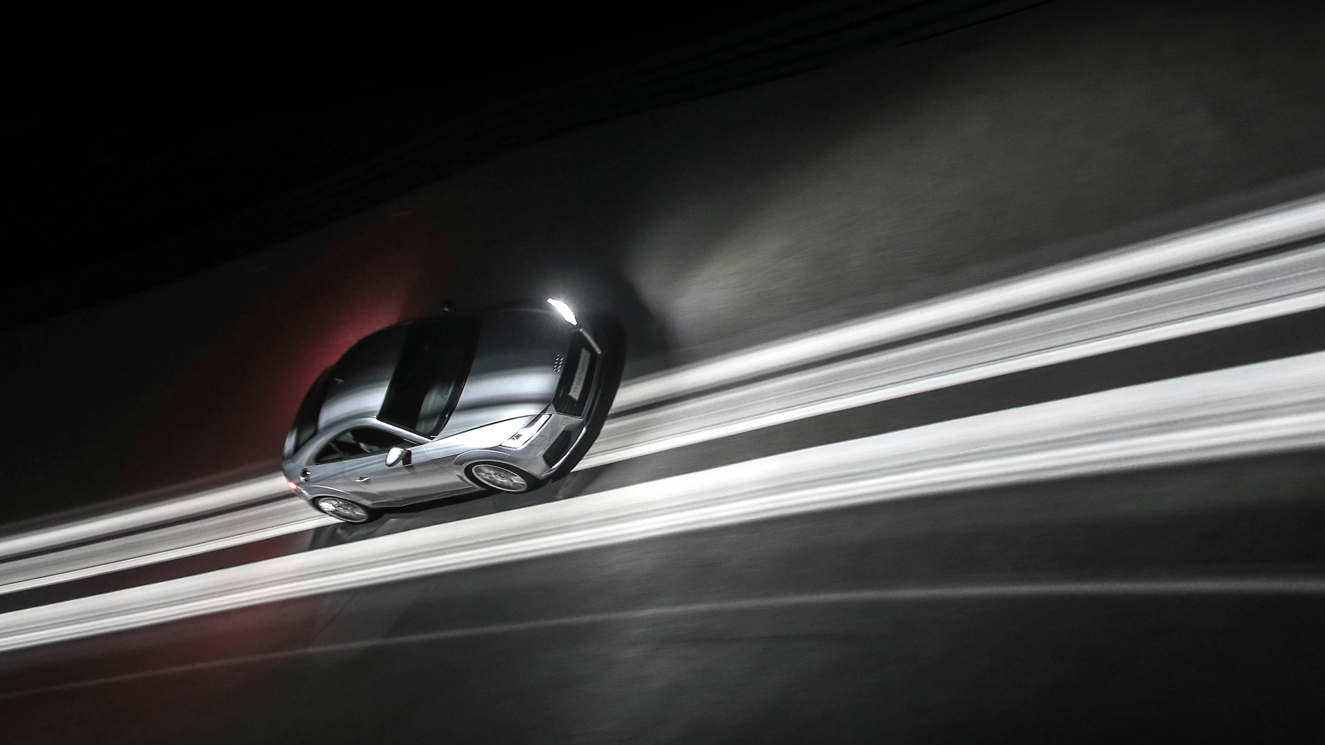 The picture shows an Audi TT racing through the curve from above.