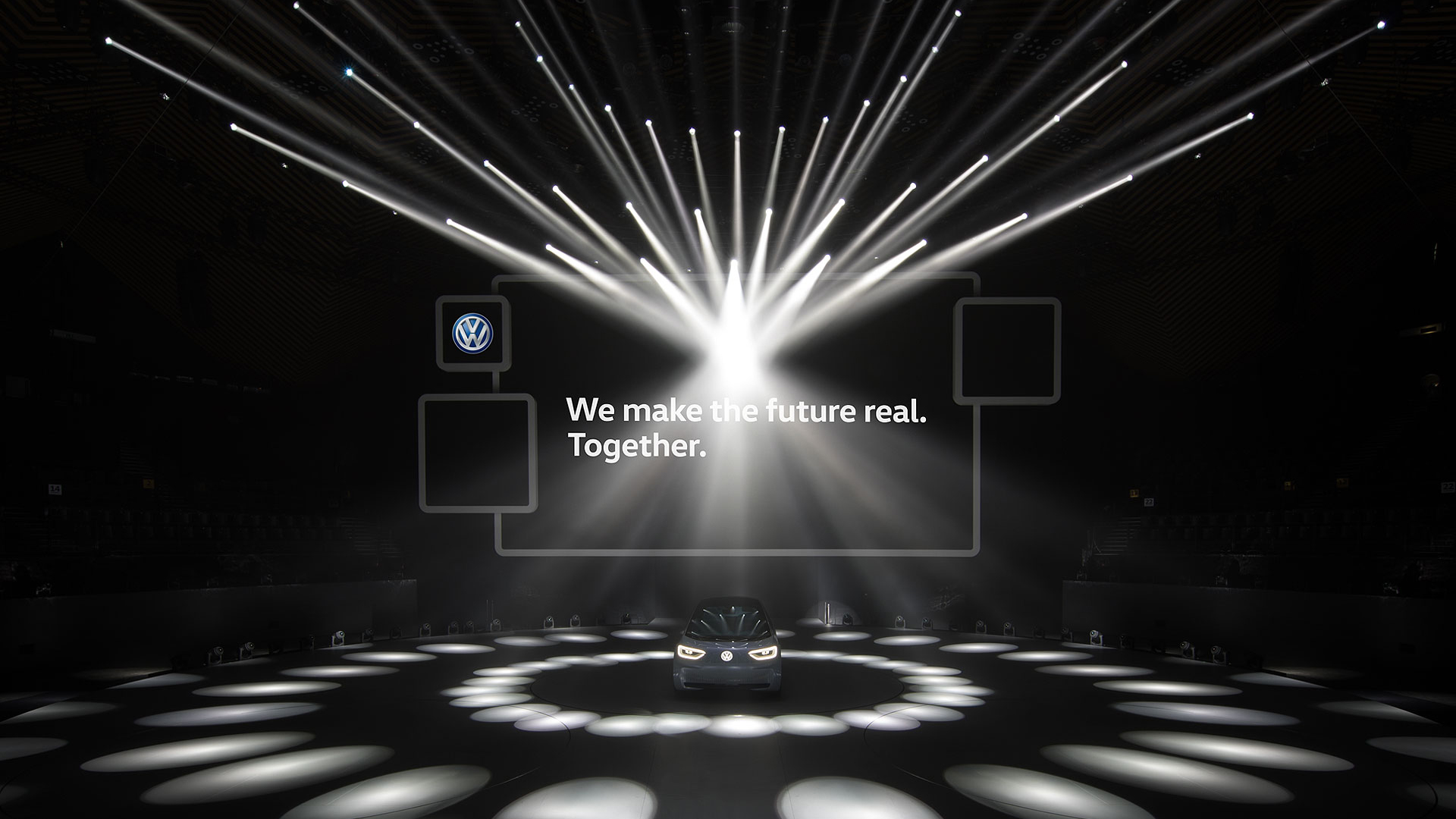 The new concept car from Volkswagen stands alone on stage and is illuminated by many light spots.
