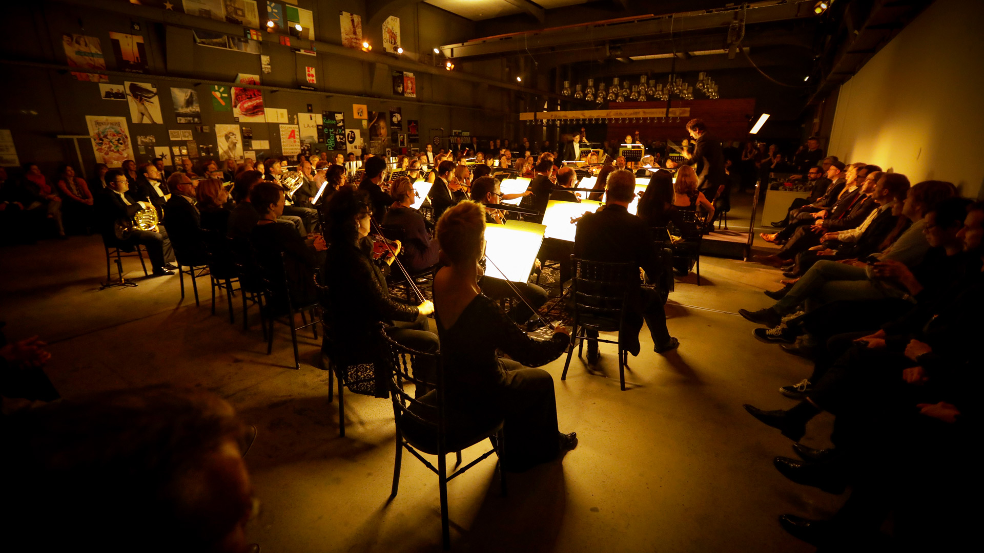 The Munich Symphony Orchestra sits in the former premises of the Blackspace agency and gives a concert. The audience either sits in between or at the side.