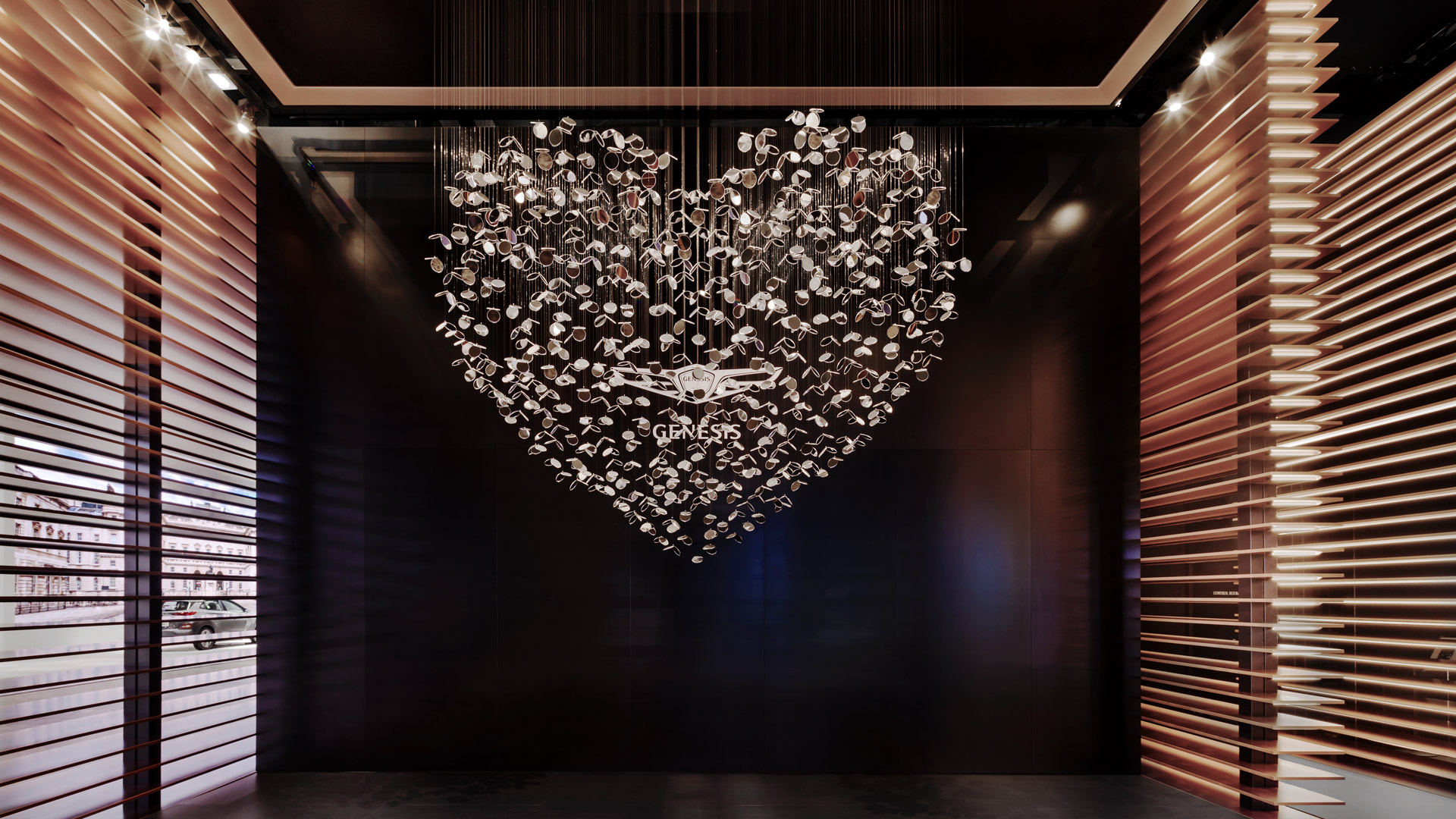 Hundreds of small pocket mirrors hang from the ceiling and form a heart sculpture.
