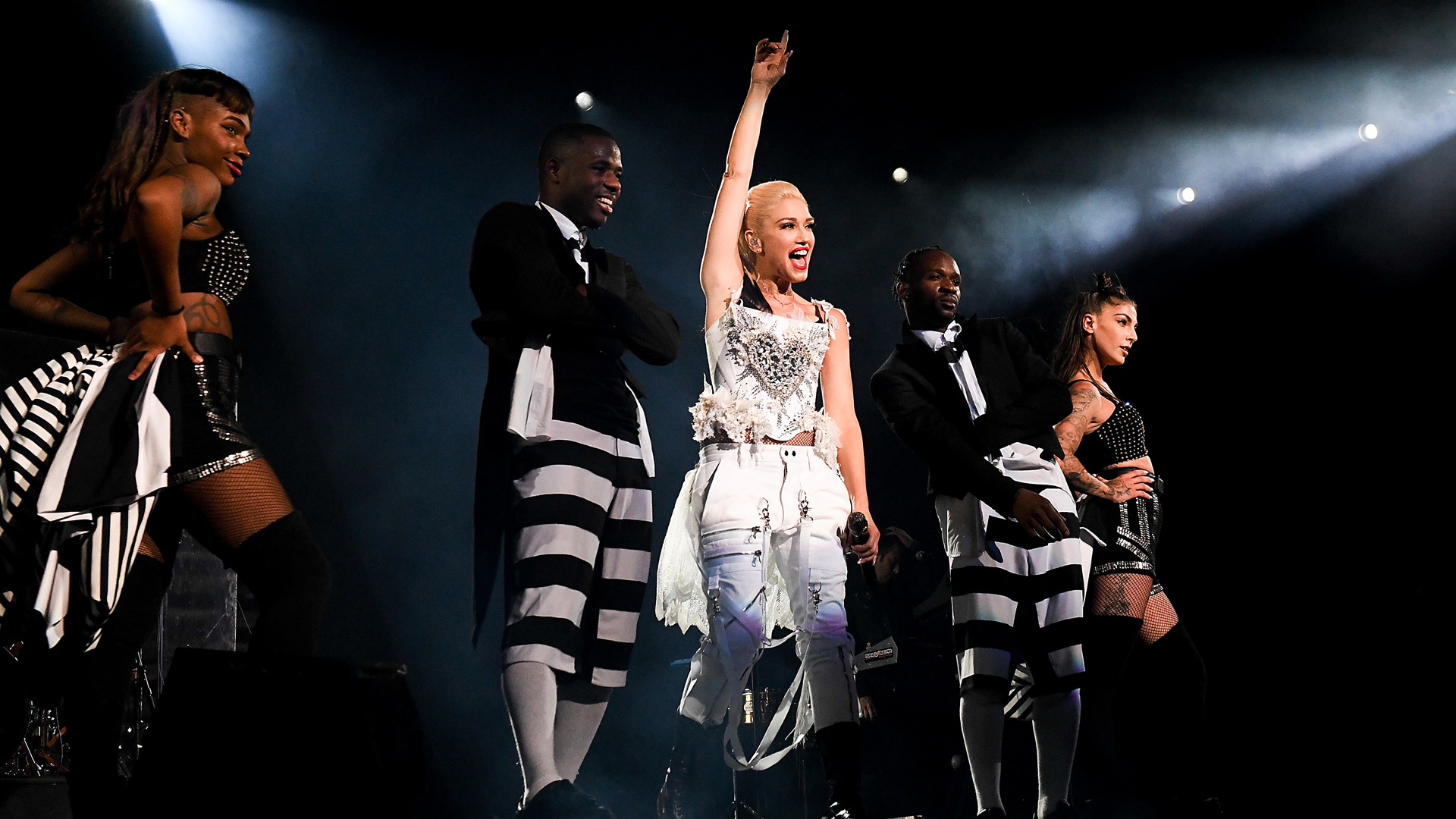 US singer Gwen Stefani stands on stage with her background dancers and happily stretches her arm into the air.