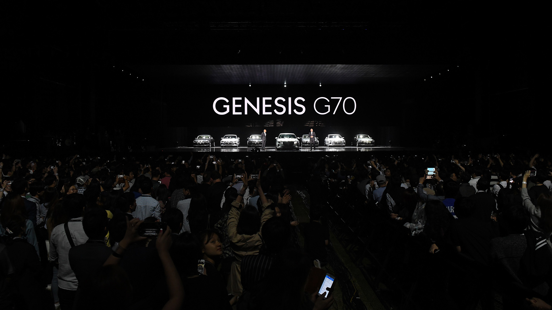Seven Genesis G70 models are standing on stage in front of a screen.