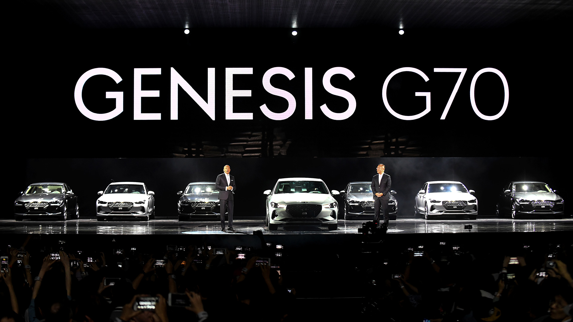 Manfred Fitzgerald and a colleague stand beside seven Genesis G70 models on stage.