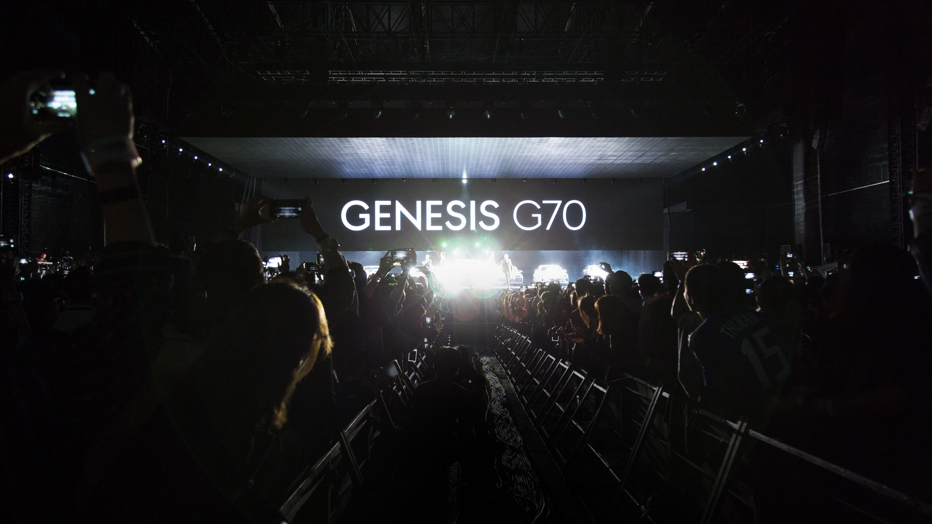 The picture shows the view from the aisle between the audience to the stage, where Genesis G70 is written in big letters.