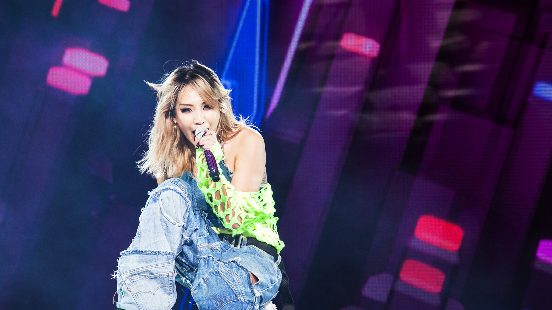 The Korean artist CL kneels on stage and sings.