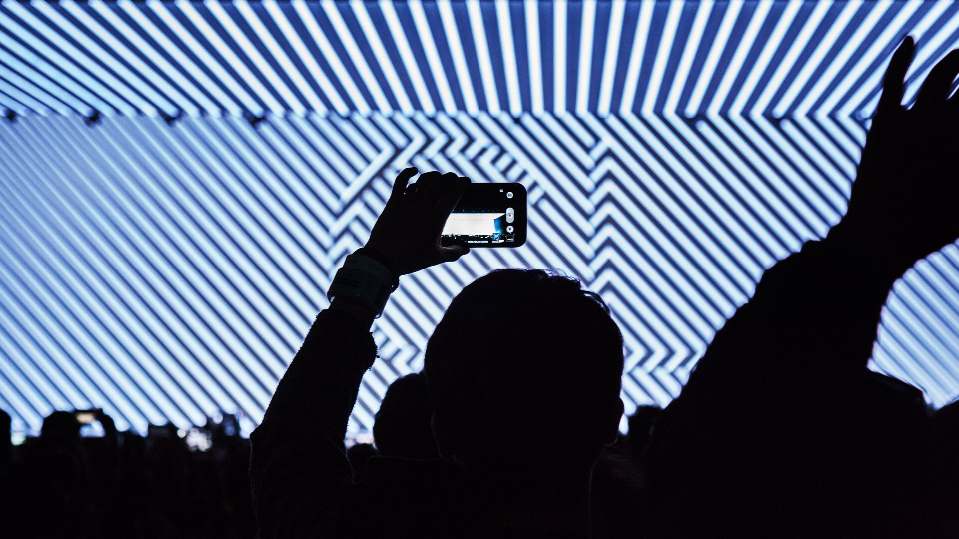 A spectator holds up his smartphone and films the stage.