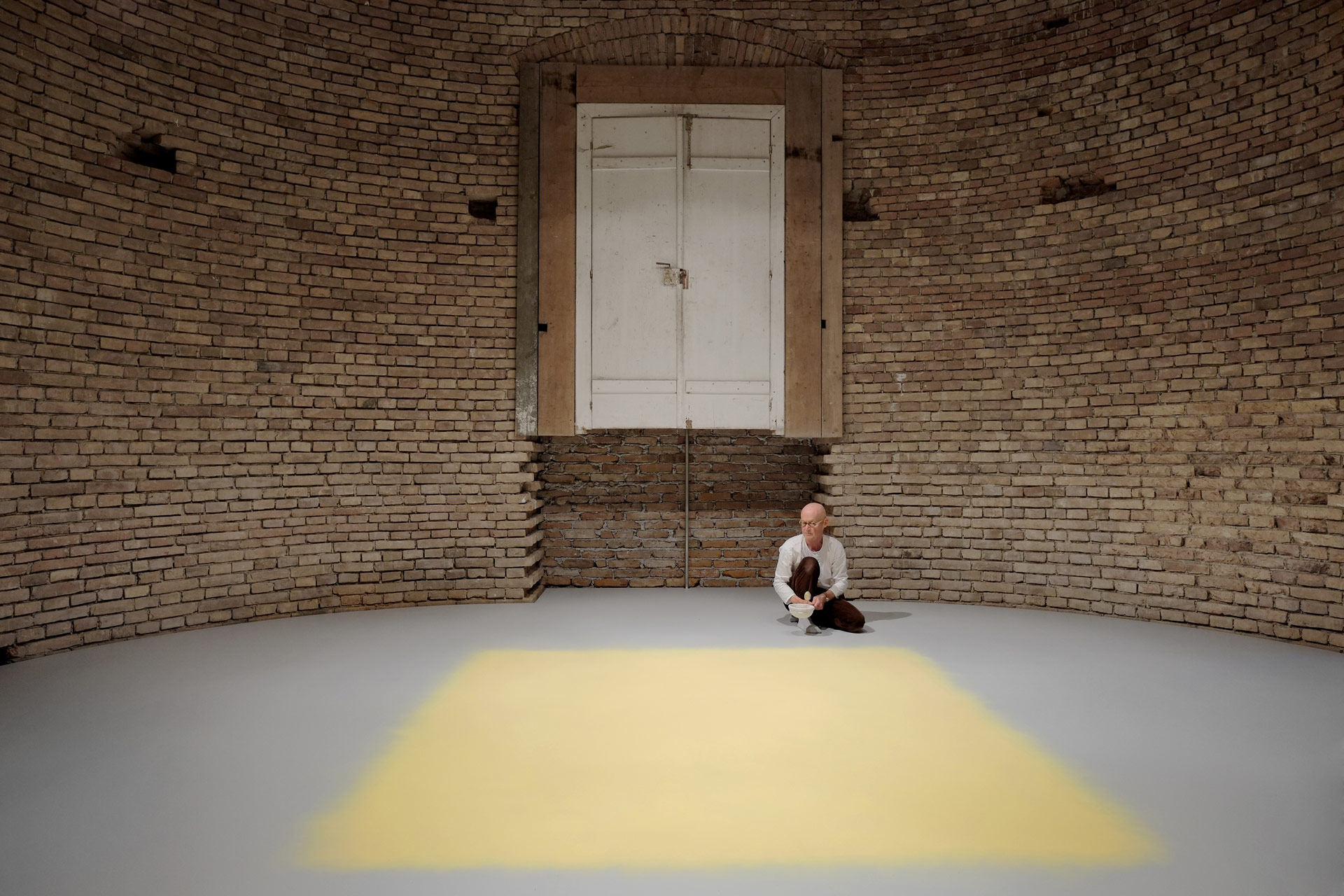 The artist Wolfgang Laib sits in front of his artwork in the unfinished rooms of Herrenchiemsee Castle.