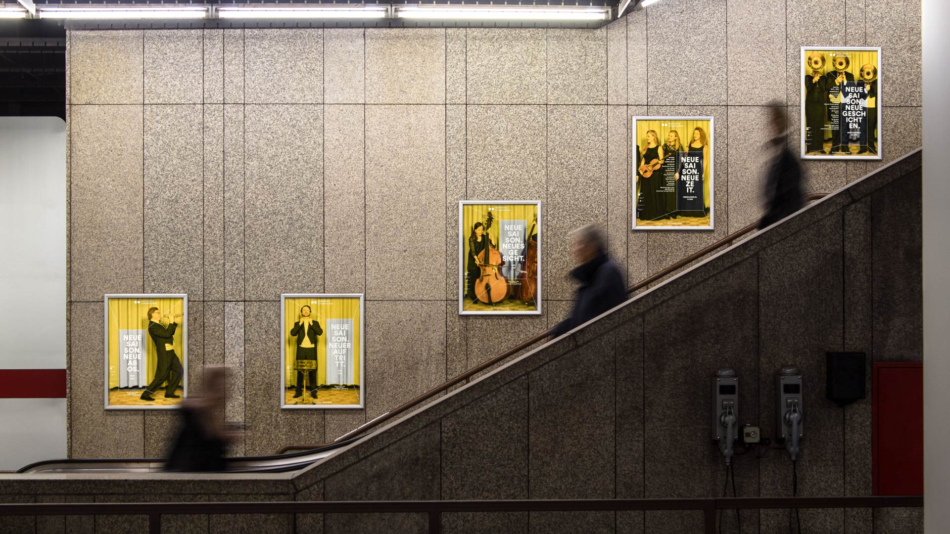 The posters of the Munich Symphony Orchestra hang next to an escalator in Munich Central Station.