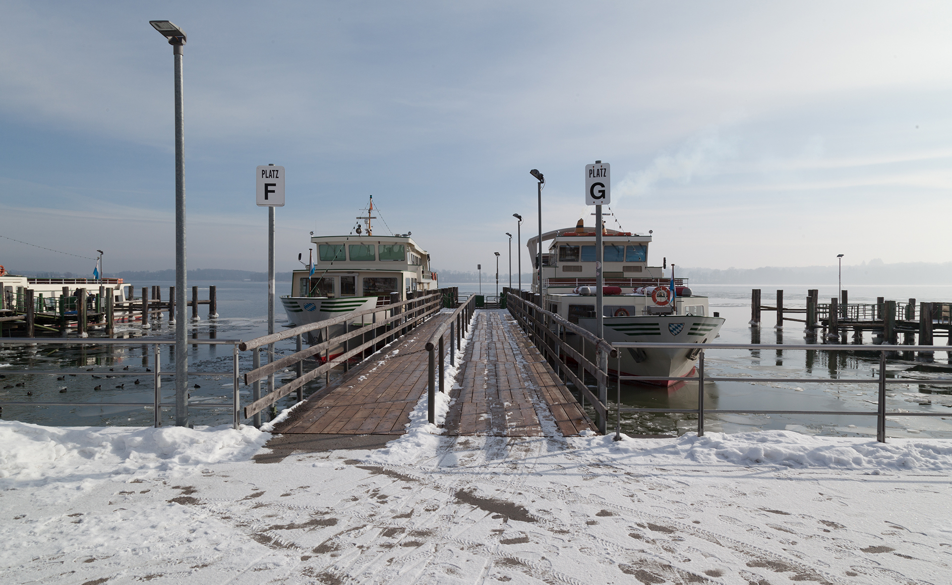 Two ships are moored at the snow-covered Chiemsee mooring.