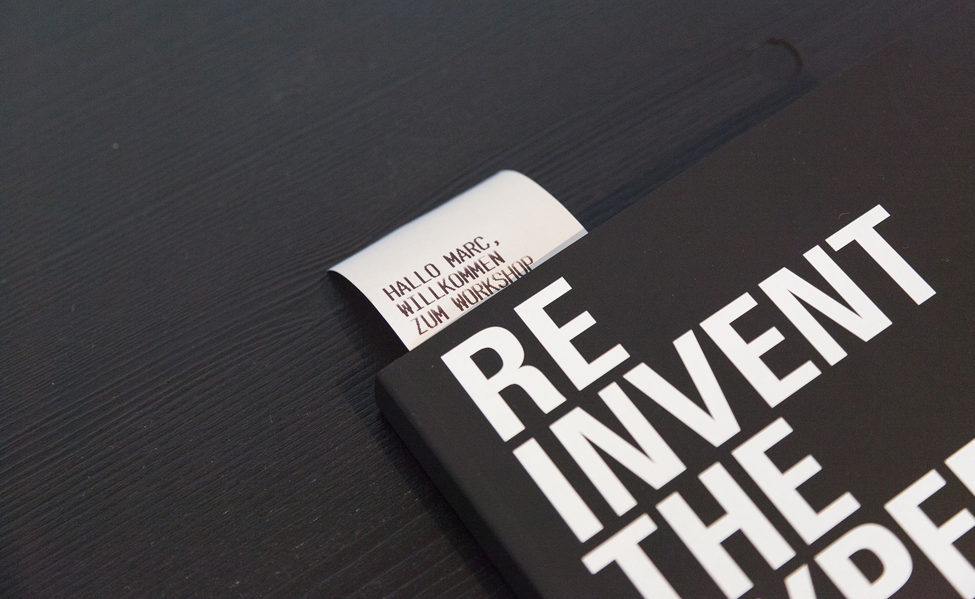 "Black notebooks with Backspace's motto ""Reinvent the experience"" are available on the table for every visitor. They contain a note that greets each participant personally."