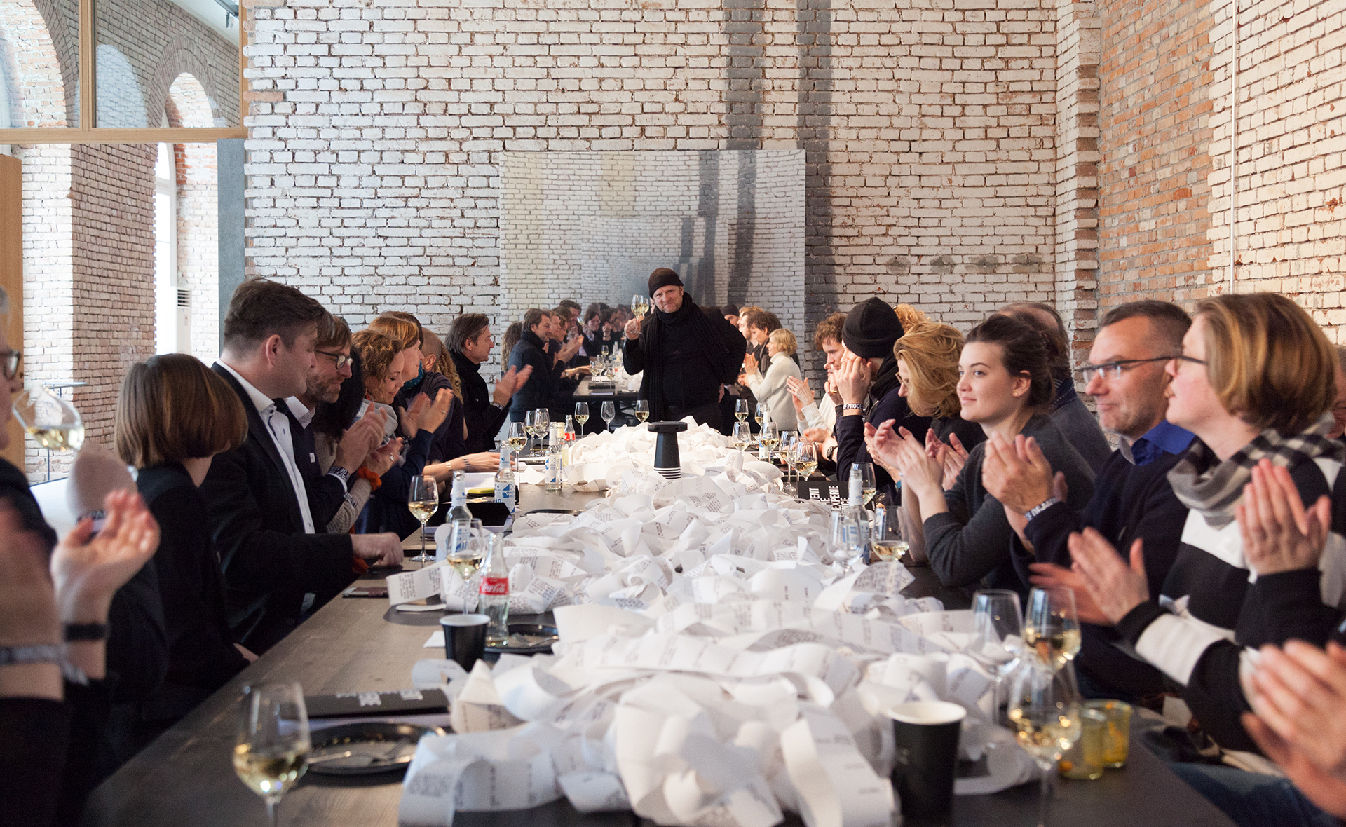 The participants clap while Designer Michael Keller stands at the end of the table and raises his glass.