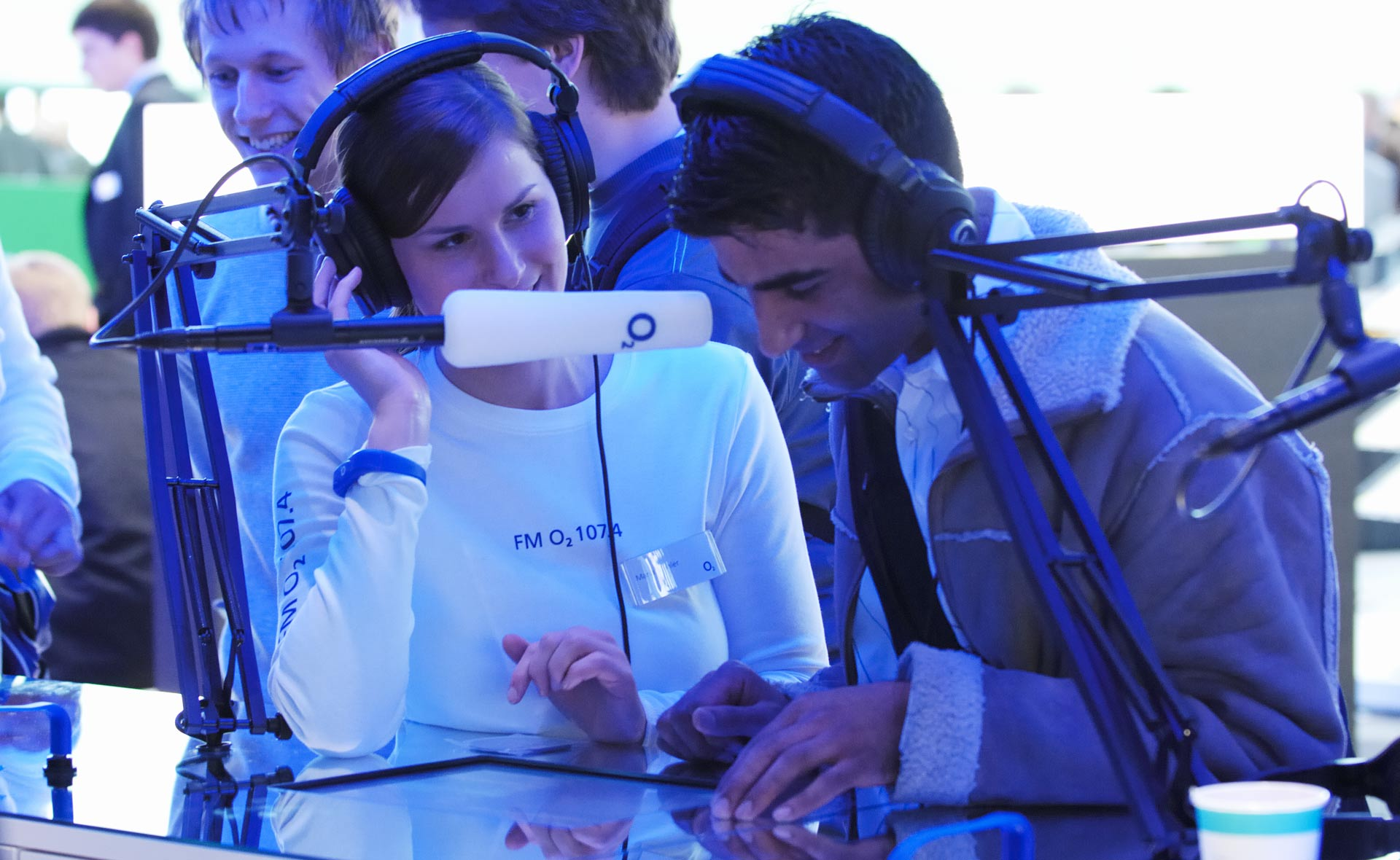 An o2 employee and a visitor wear headphones and speak into a microphone.