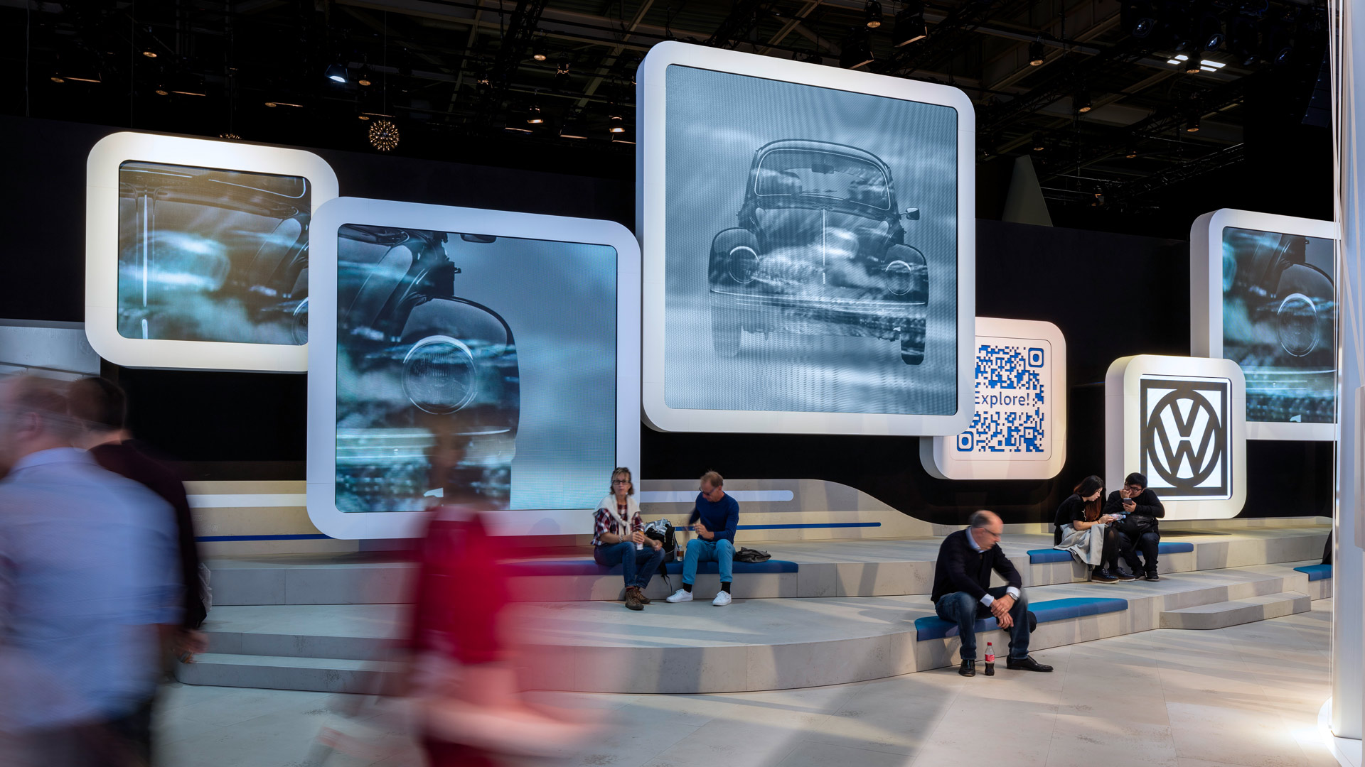 Visitors sit in front of big pictures of the old VW Beetle and take a break.