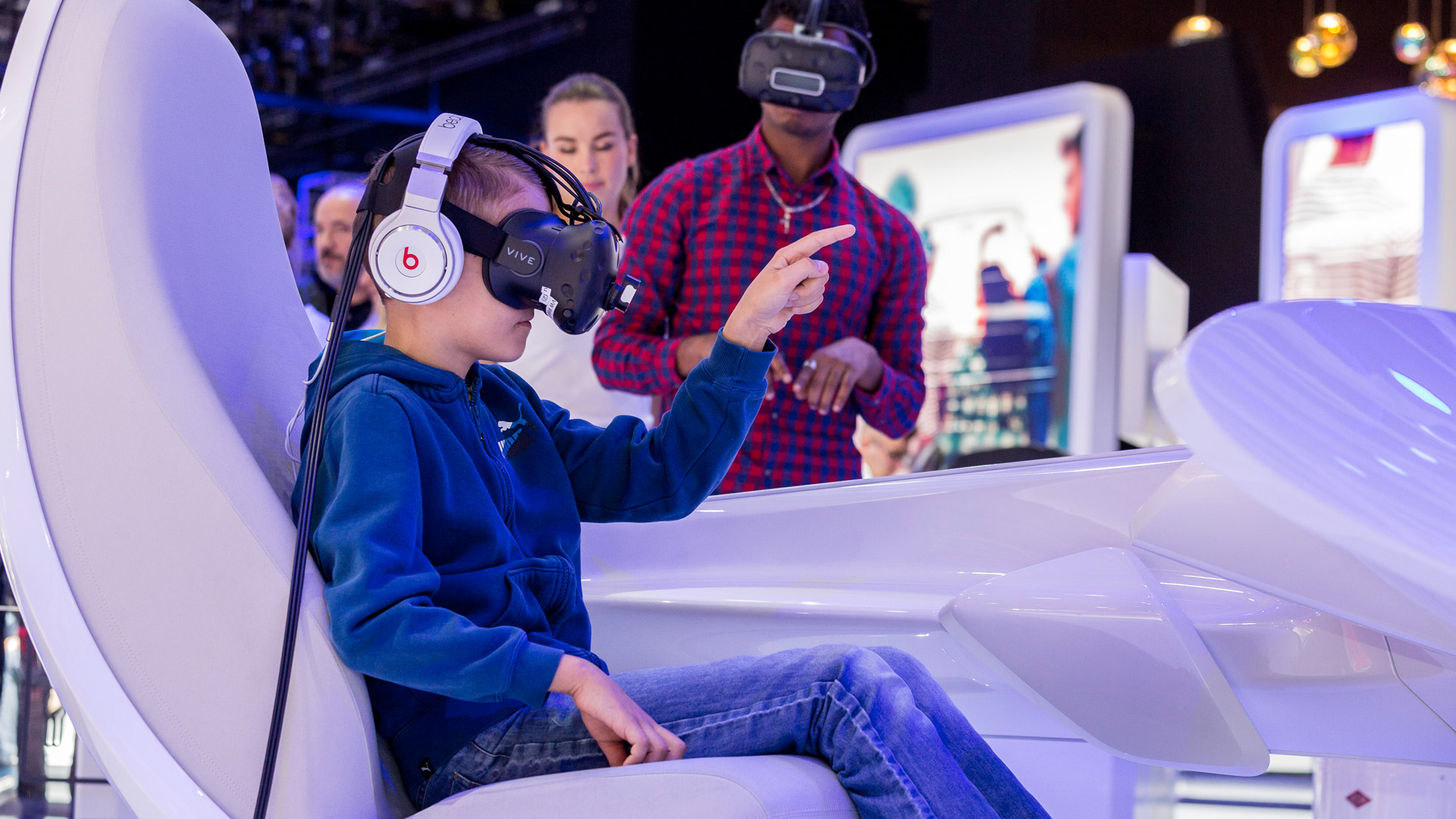 A little boy wears virtual reality glasses and points his finger.