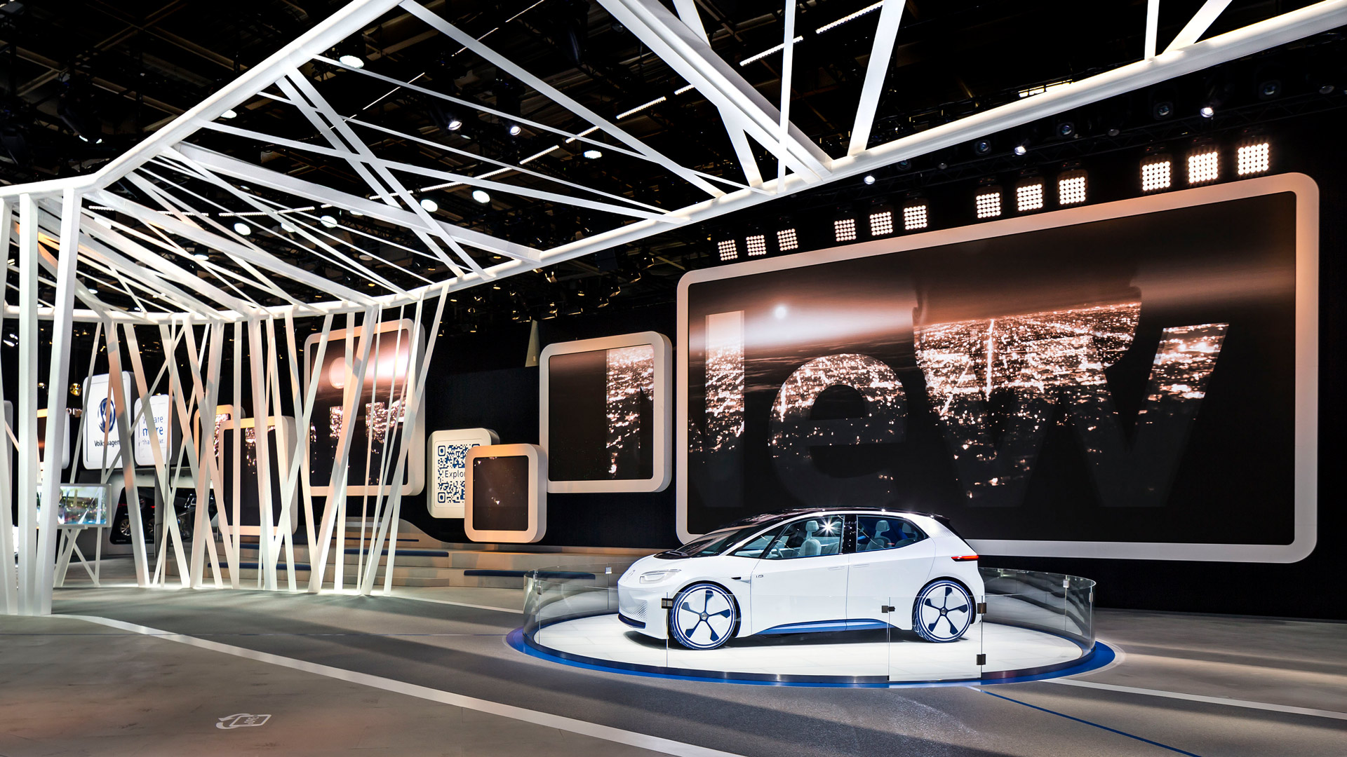 The picture shows the concept car of Volkswagen, which stands separated in front of a big screen.