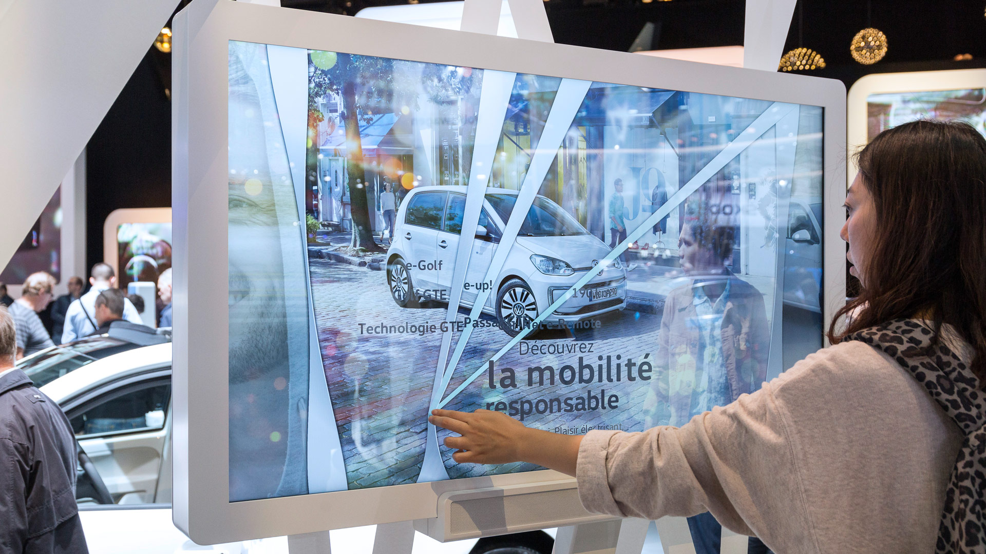 A female visitor drives her finger over a touch screen and learns more about the new VW up.