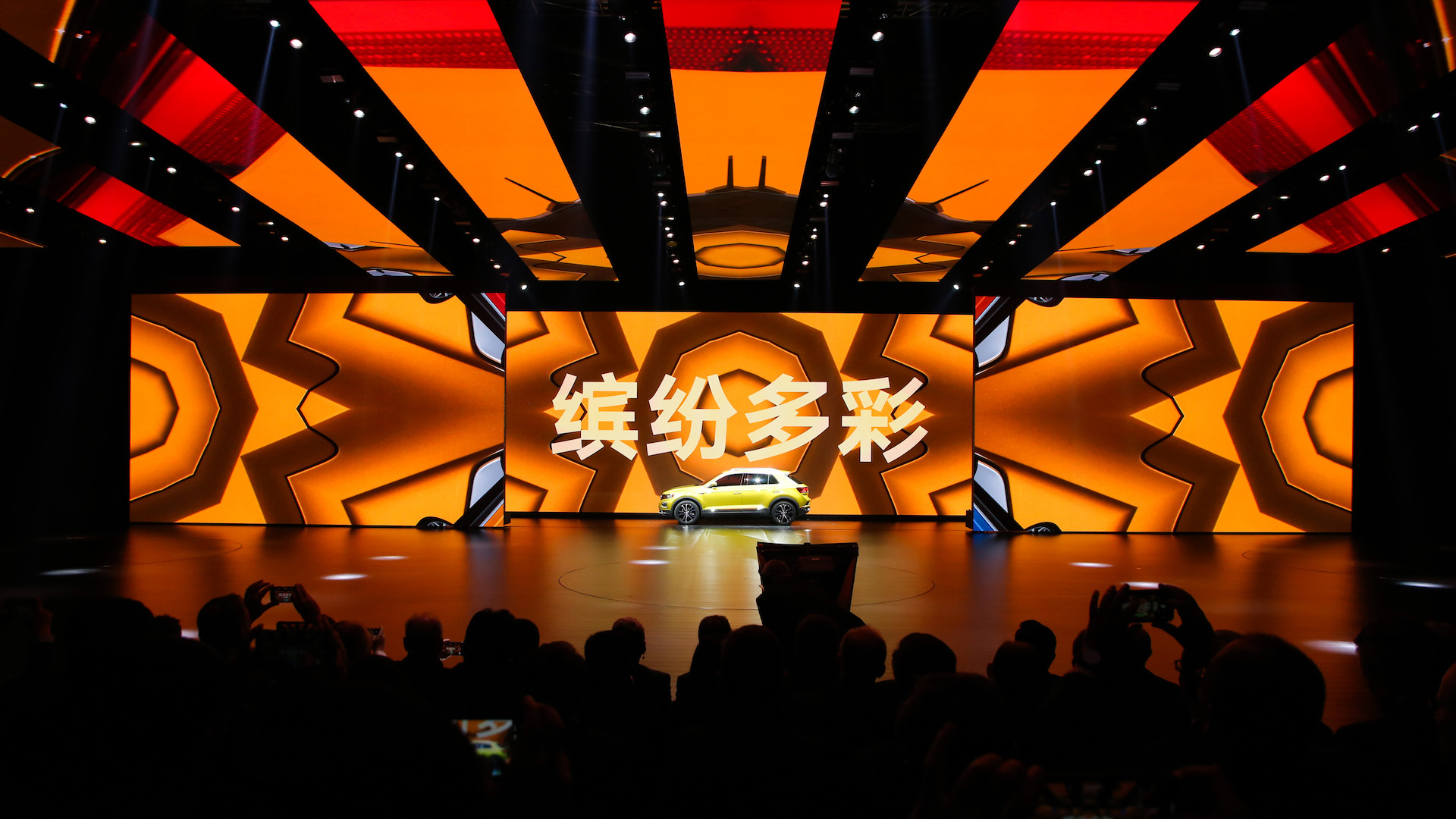 A yellow car stands in front of an orange LED wall.