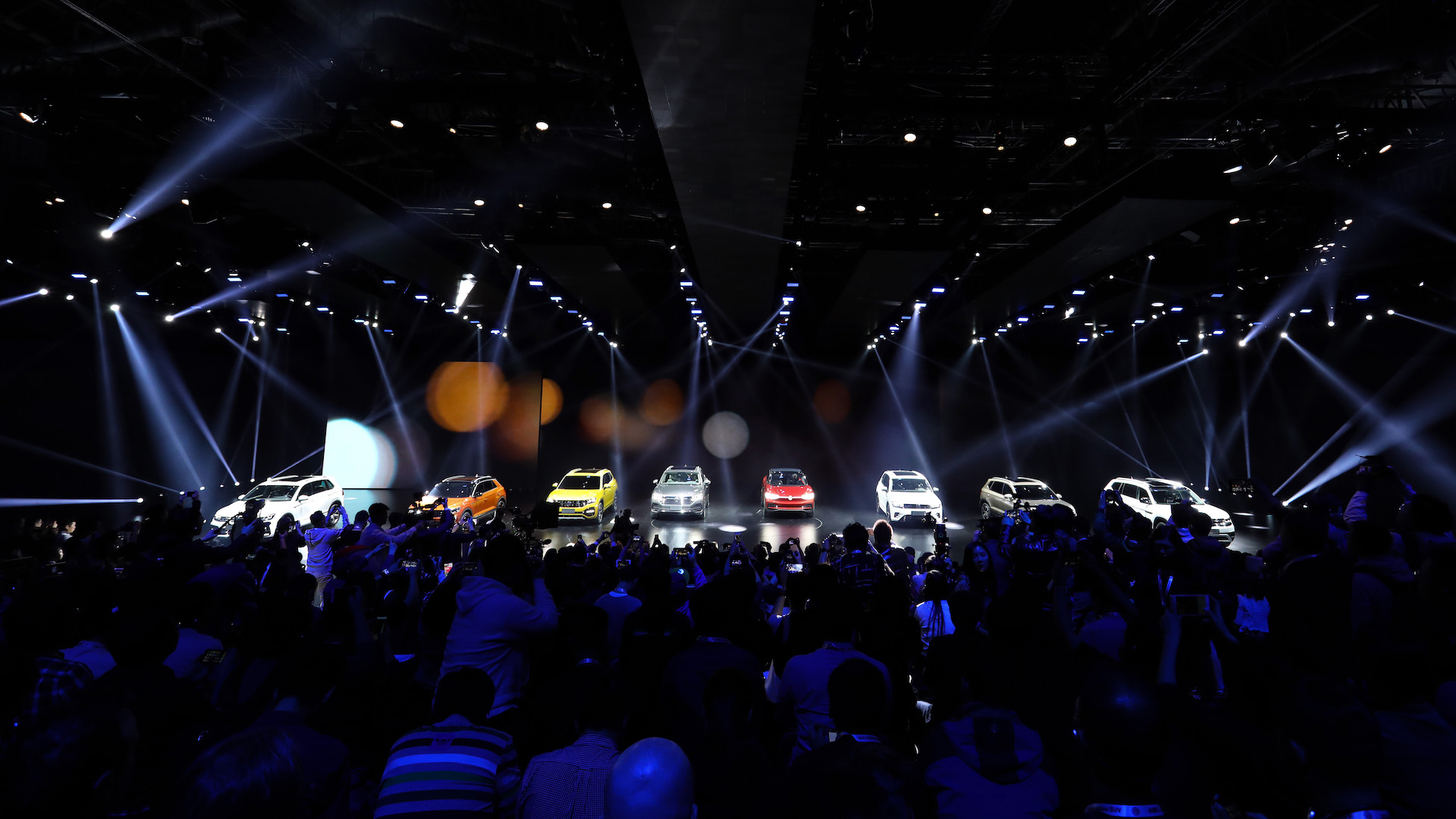 The eight new Volkswagen SUV models stand in front of a black stage and are illuminated.