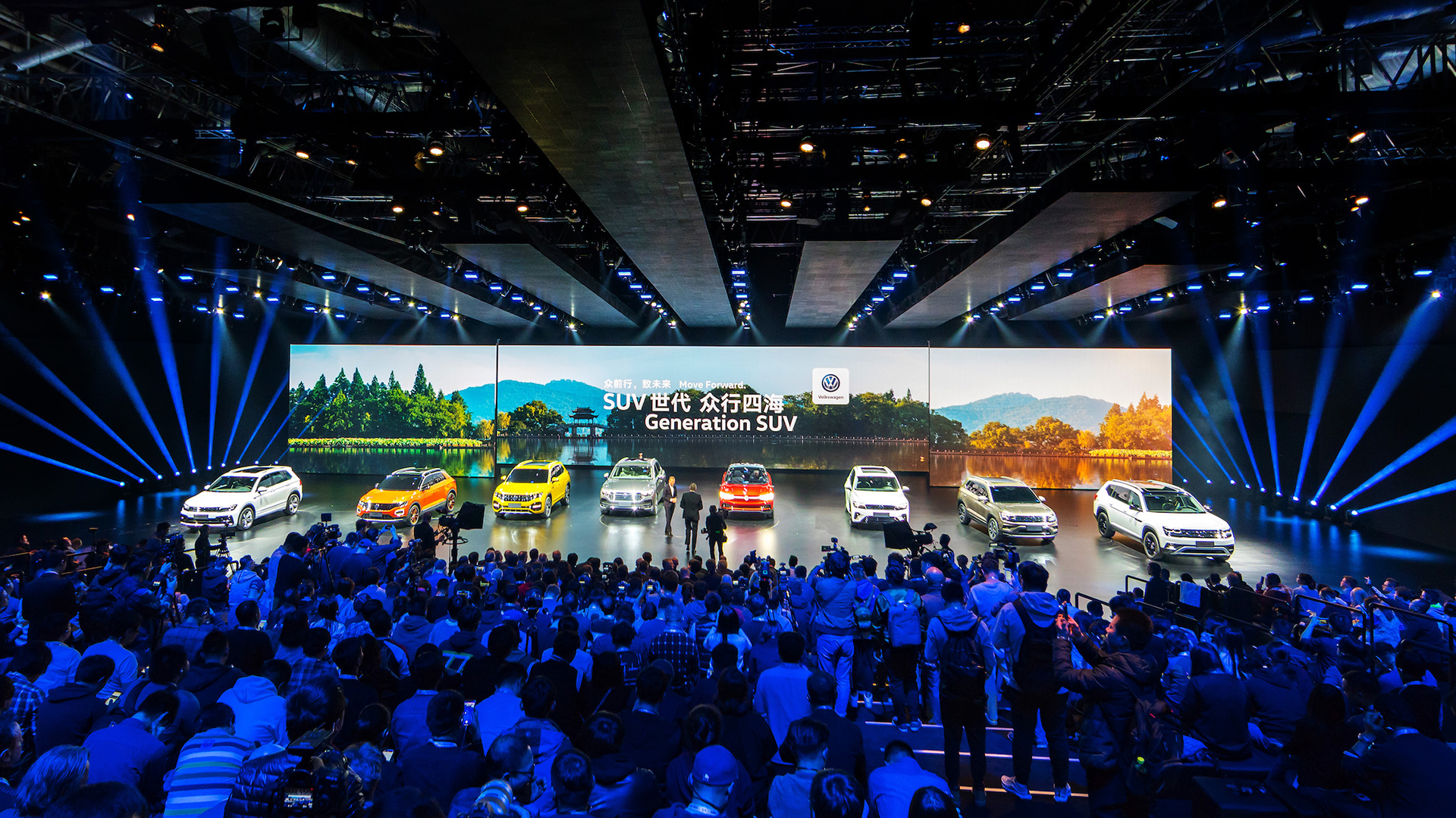 Eight new Volkswagen SUVs stand on stage in front of a large LED screen.
