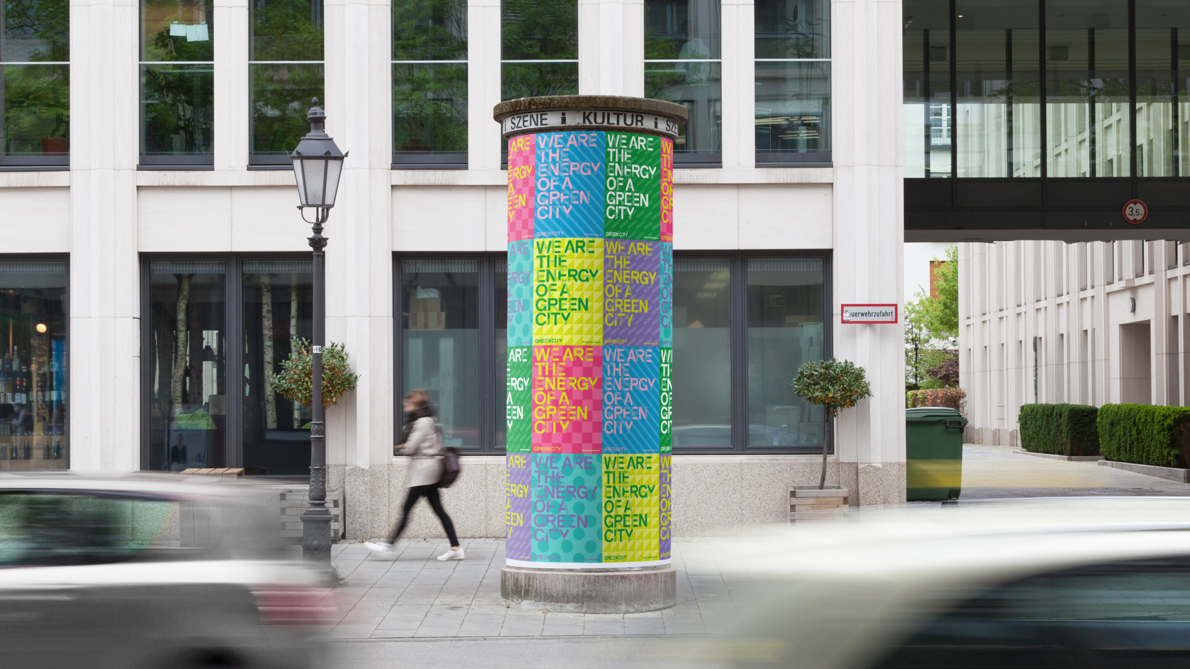 Many colourful Green City posters stick to an advertising pillar in Munich.