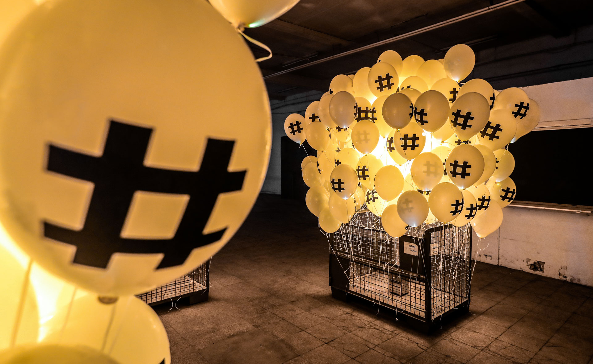On the picture you can see many yellow balloons with a hash tag on it, which are attached to a mesh box.