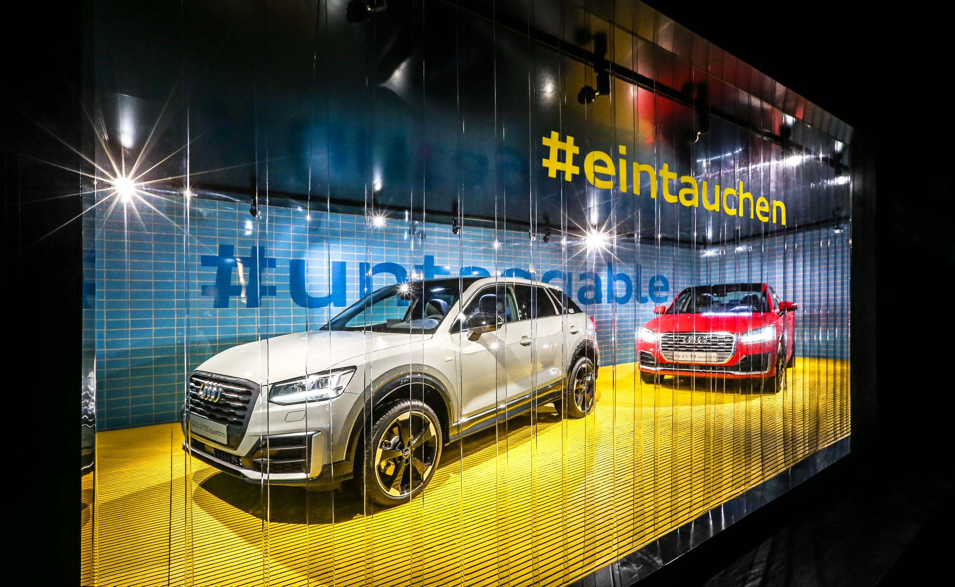 A grey and a red Audi Q2 seem to be standing in a swimming pool. In front of it is written in yellow #dipping.