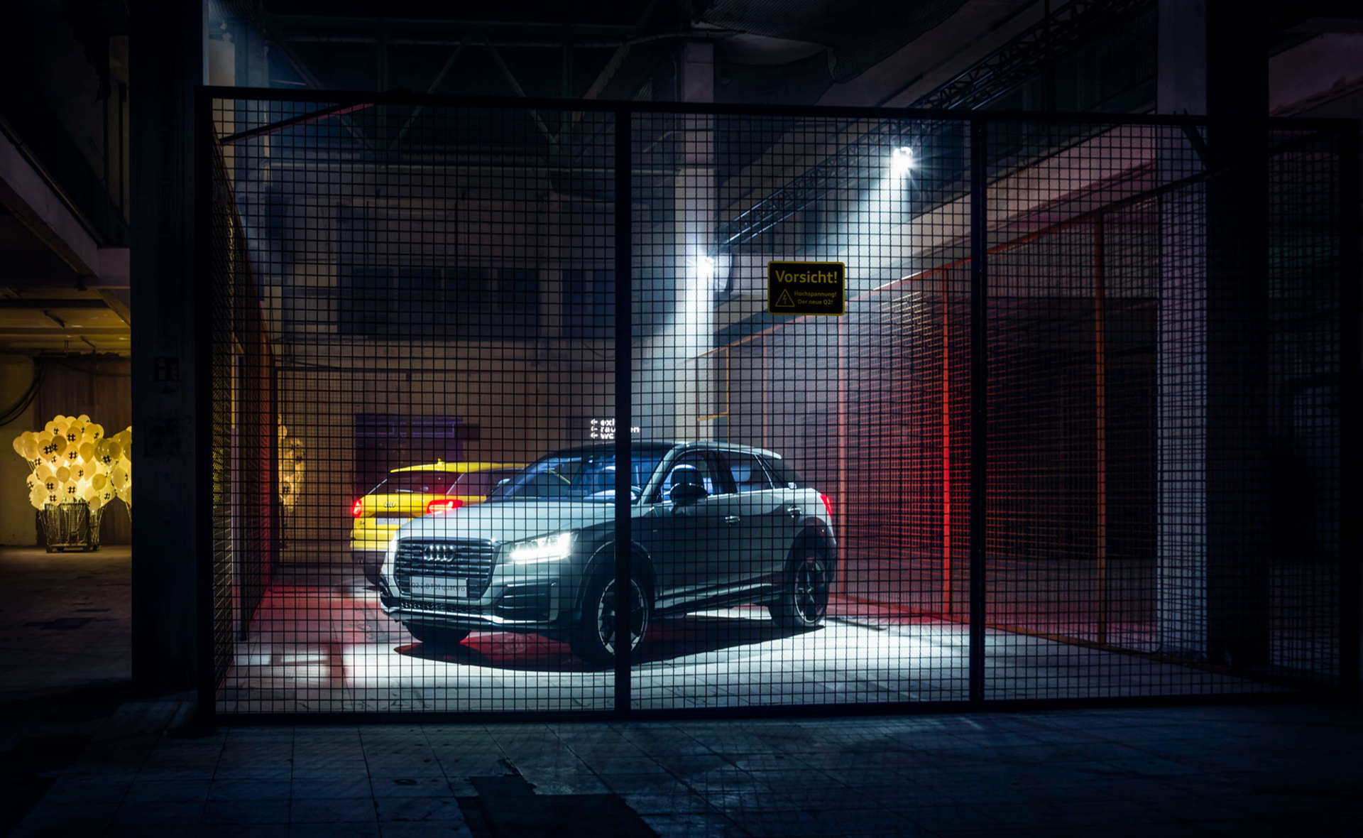 A yellow and a grey Audi Q2 stand in a weakly lit steel cage.