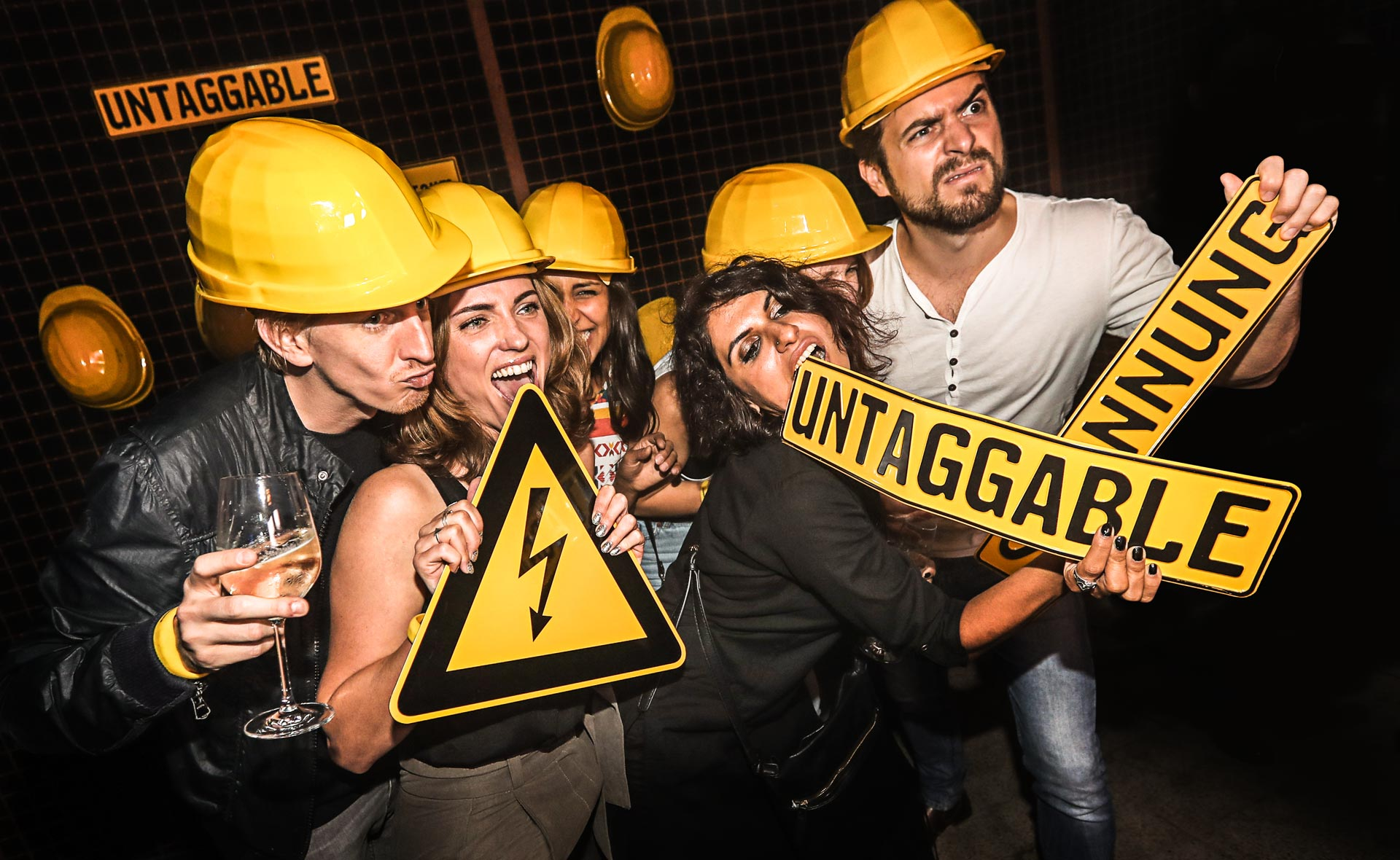 "Six party guests wear yellow construction helmets and hold signs with the word ""untaggabble"" in the cameras."
