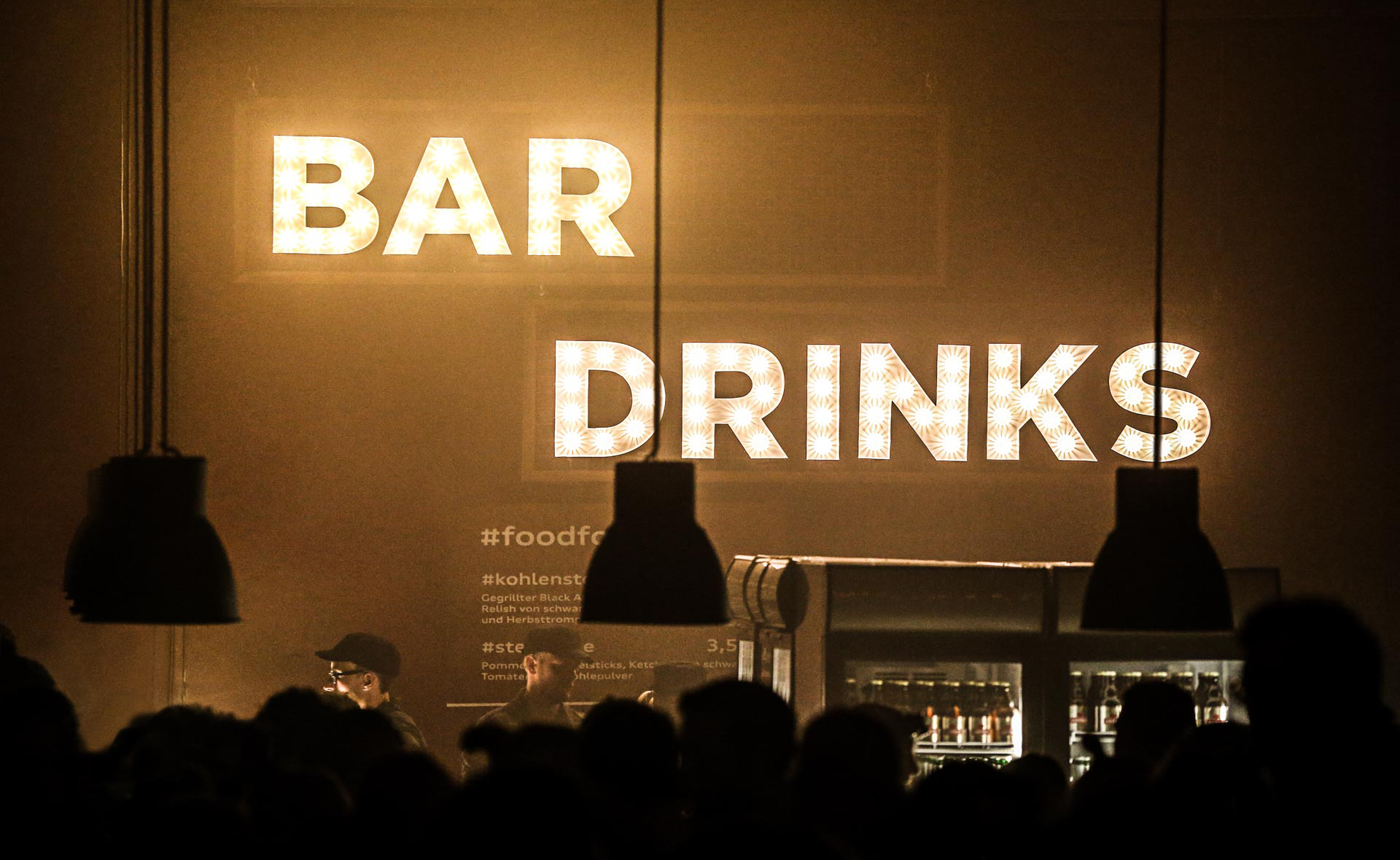 "A light installation consisting of the words ""bar"" and ""drinks"" hangs above a bar."