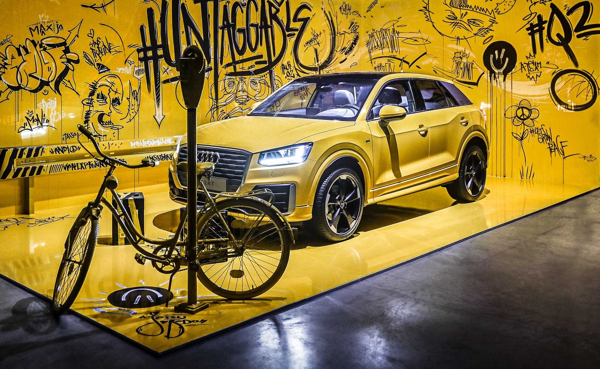 A yellow Audi Q2 stands in front of a yellow wall full of graffiti. In front of it stands a yellow parking meter and a yellow bicycle.