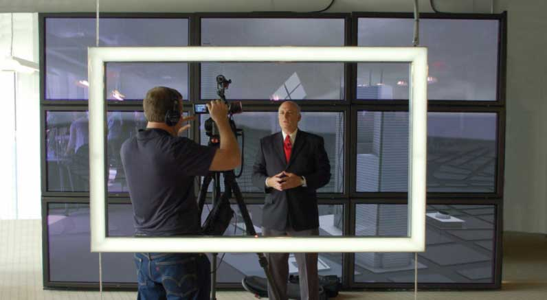 A man in a suit and tie is interviewed behind the frame by a cameraman.